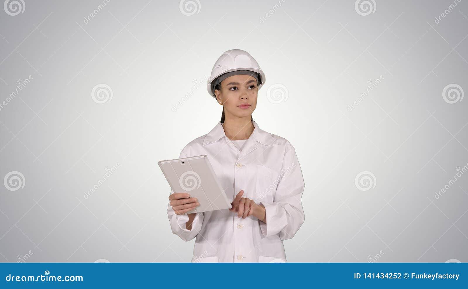 Инженер женщины проверяя информацию и объекты на ее планшете на предпосылке градиента