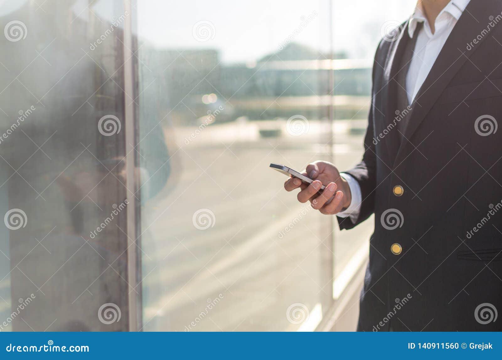 Идя бизнесмен используя снаружи смартфона