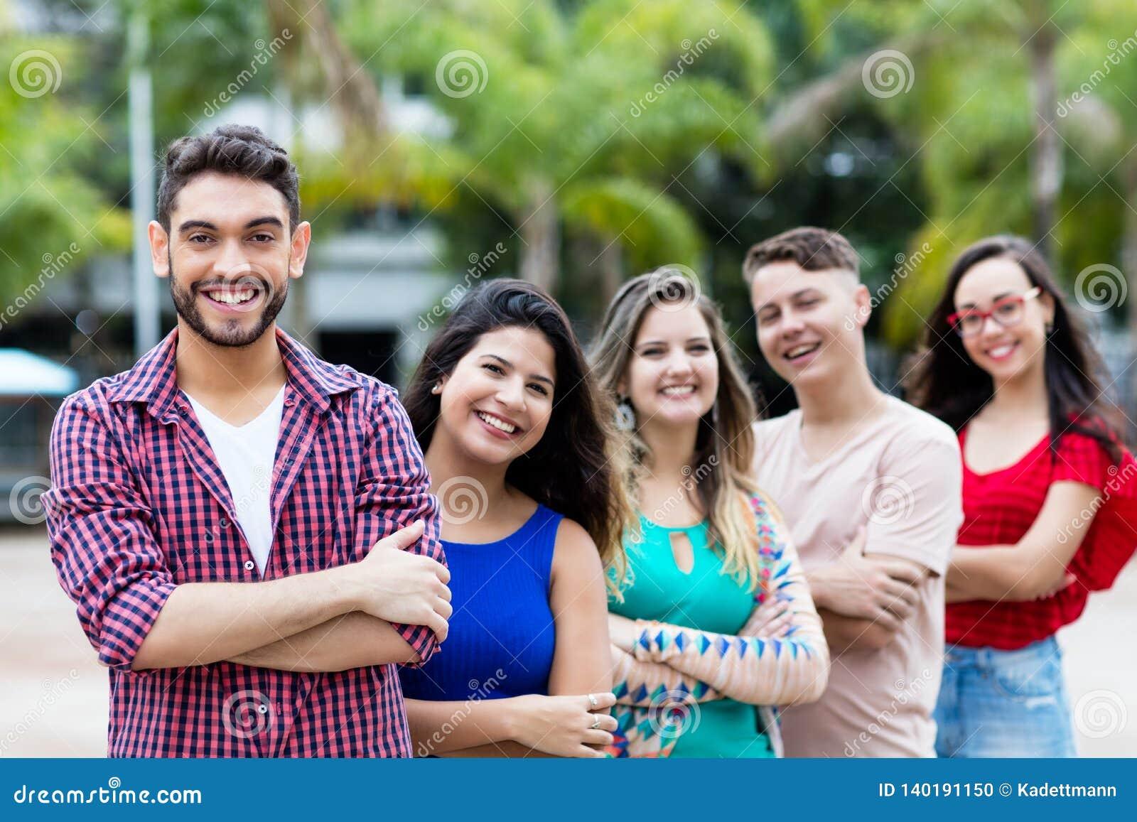 Испанский человек хипстера с мужскими и женскими молодыми взрослыми в линии