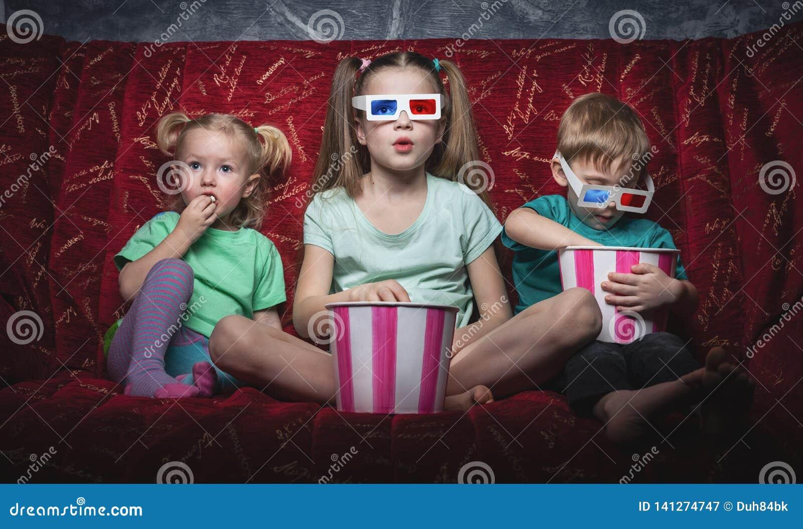 Кино детей: Дети сидят на красной софе и смотрят фильм 3D