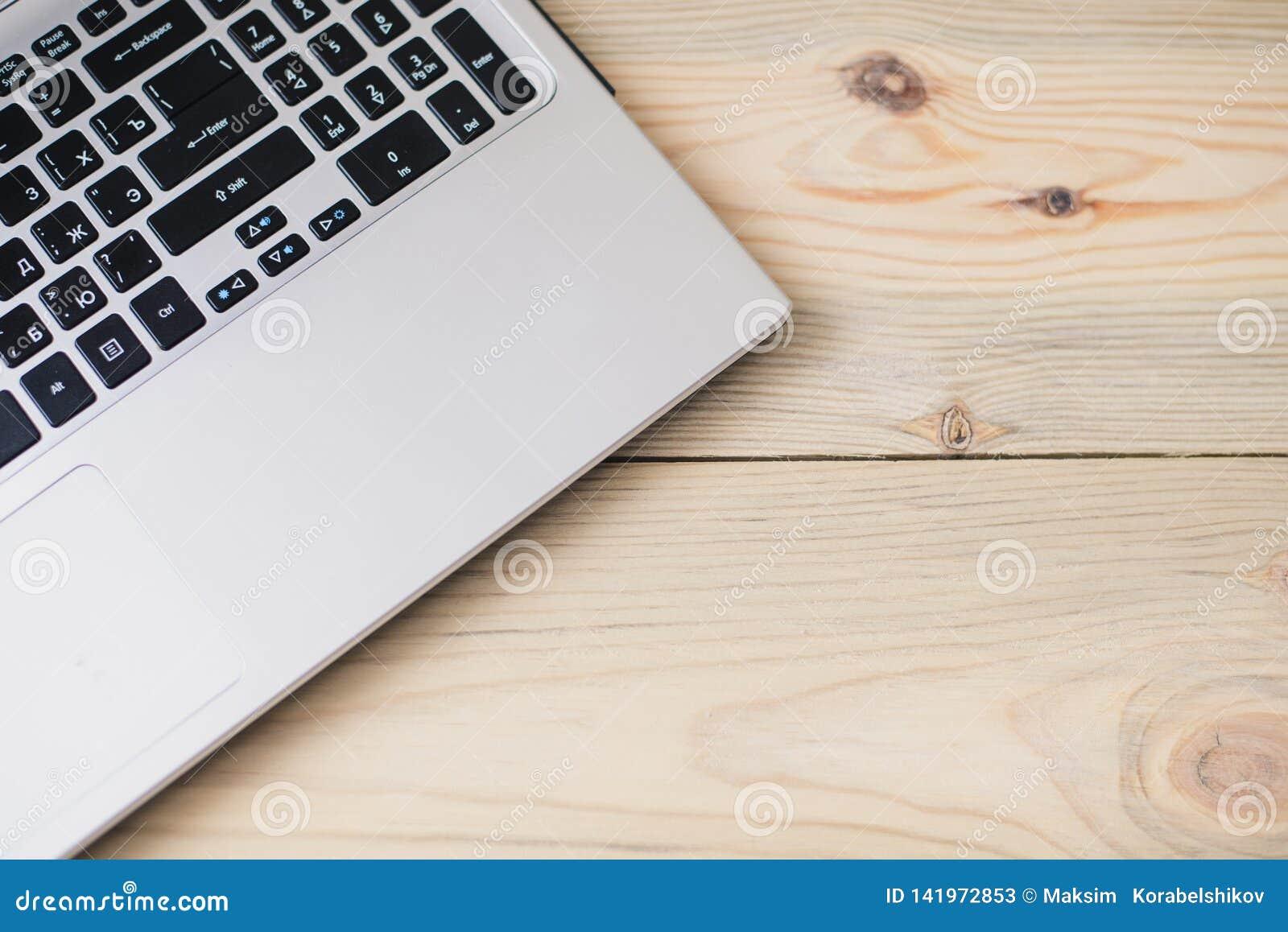 Клавиатура ноутбука взгляда сверху на деревянной предпосылке