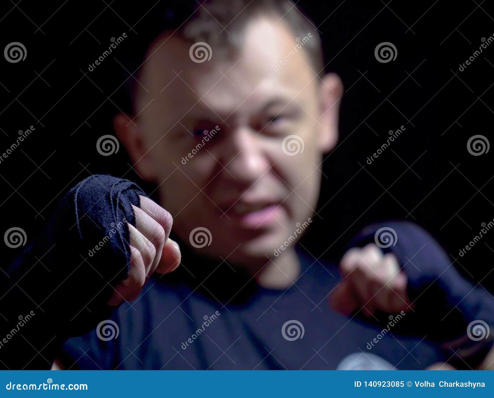Кулак агрессивное молодое мужского, конец-вверх, запачканная предпосылка