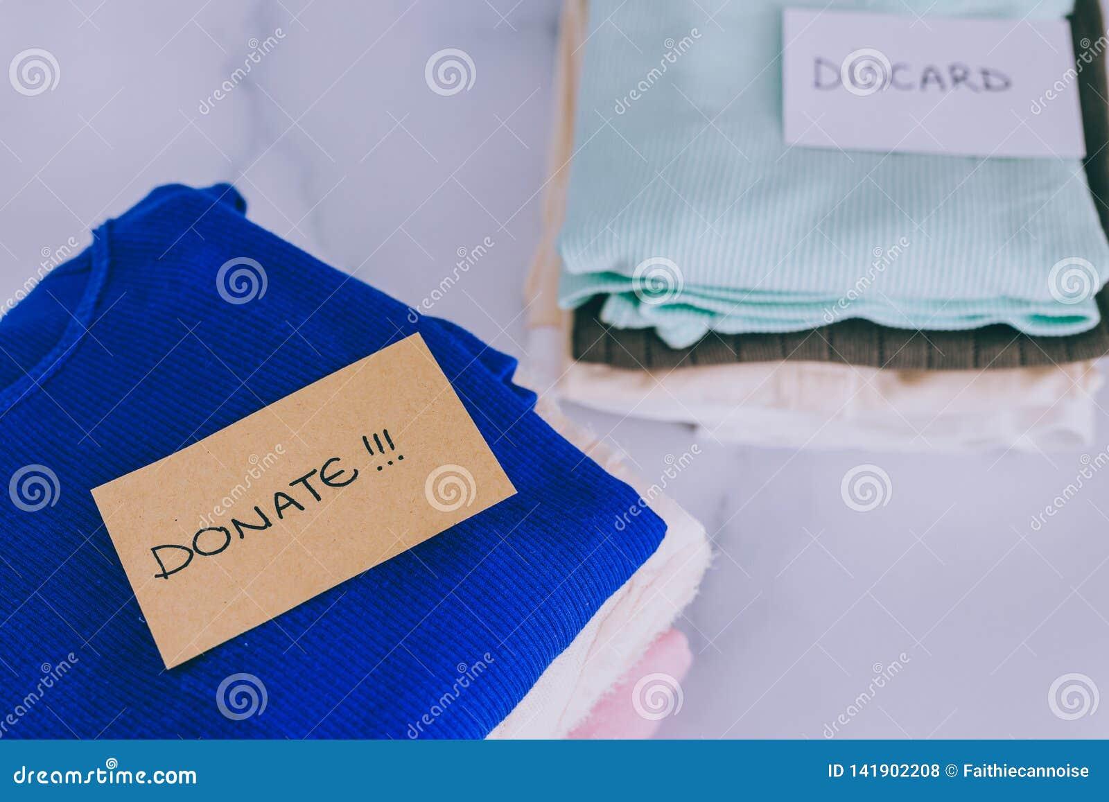 Кучи футболок и одежд будучи сортированными в держат сбрасывание и дарят категории