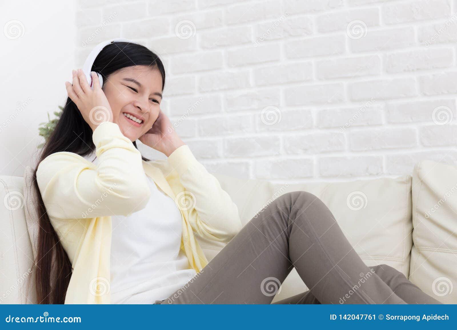 Красивая азиатская молодая женщина насладиться слушает музыка с наушниками на софе дома в живущей комнате