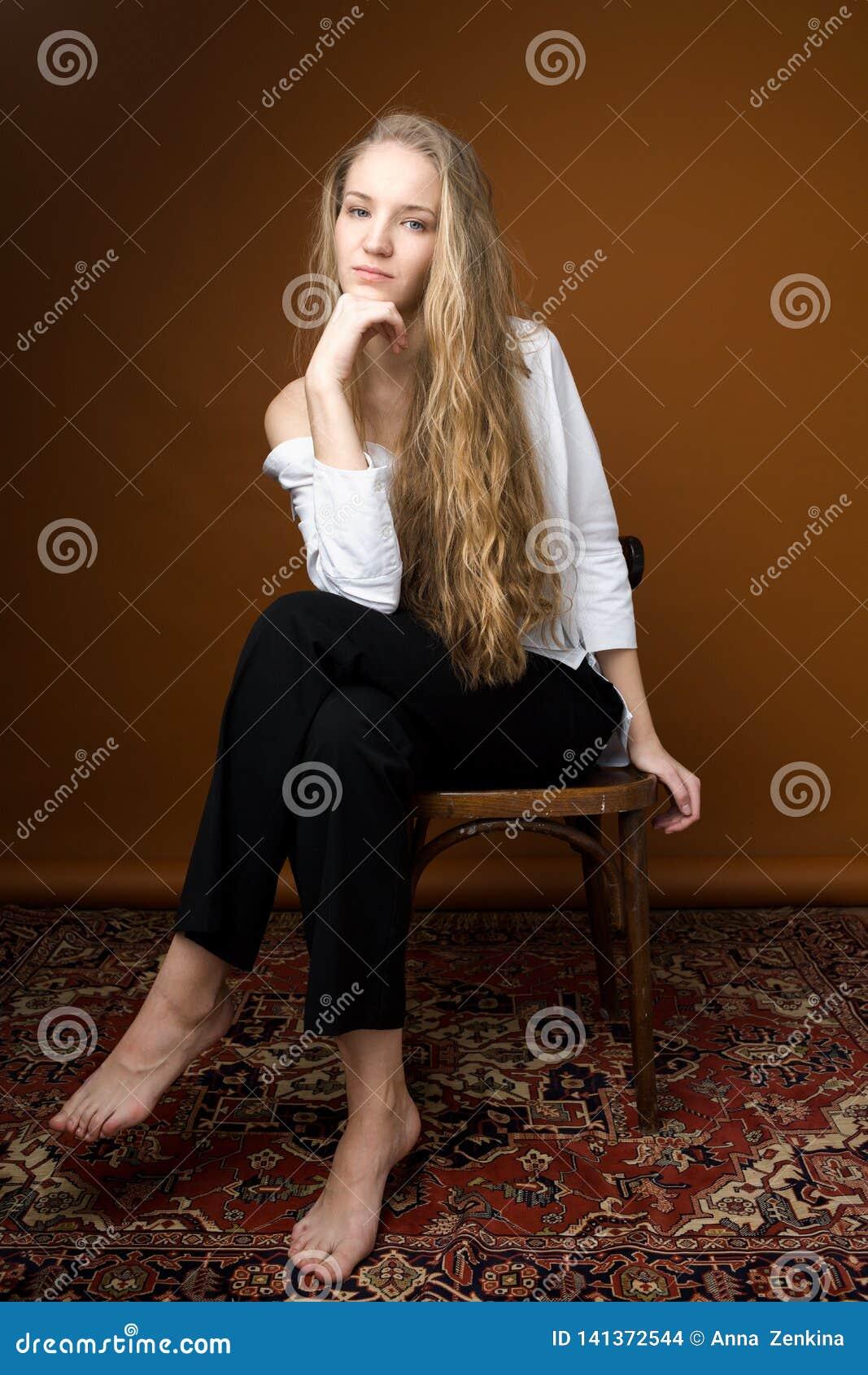 Красивая внимательная модель в белой рубашке и черных брюках