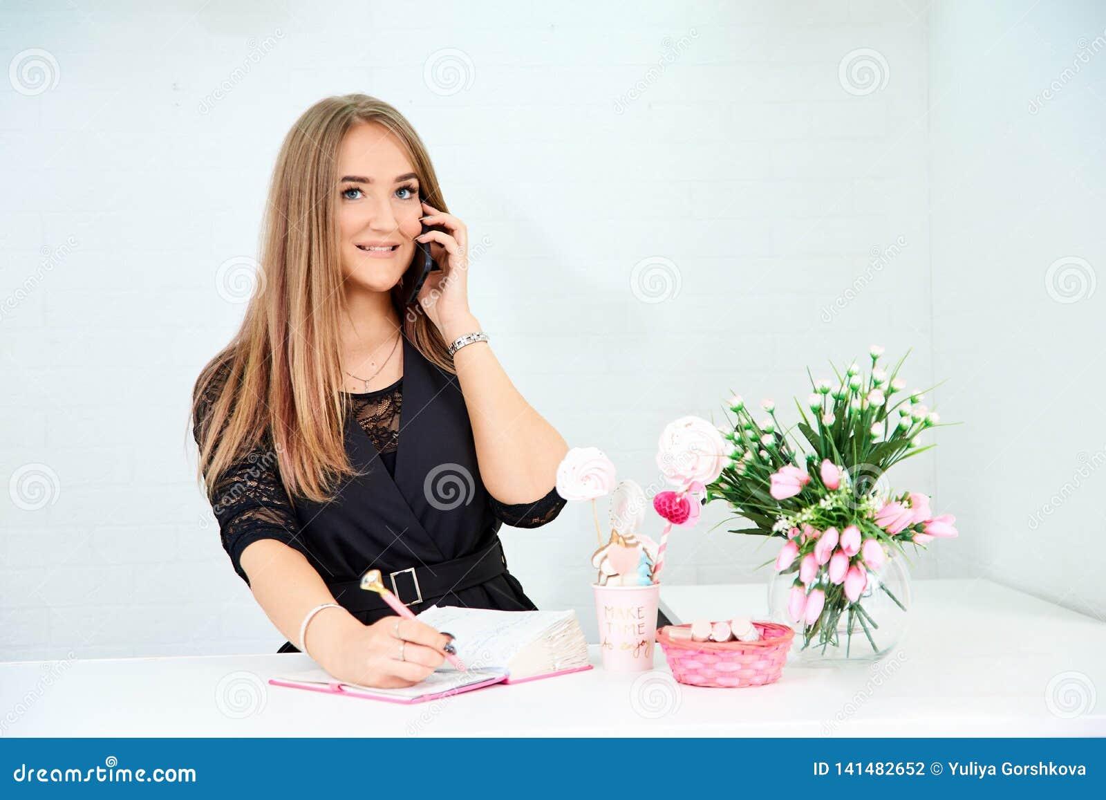 красивая европейская девушка принимает звонок по телефону и пишет в тетради на белой предпосылке Рядом цветки и