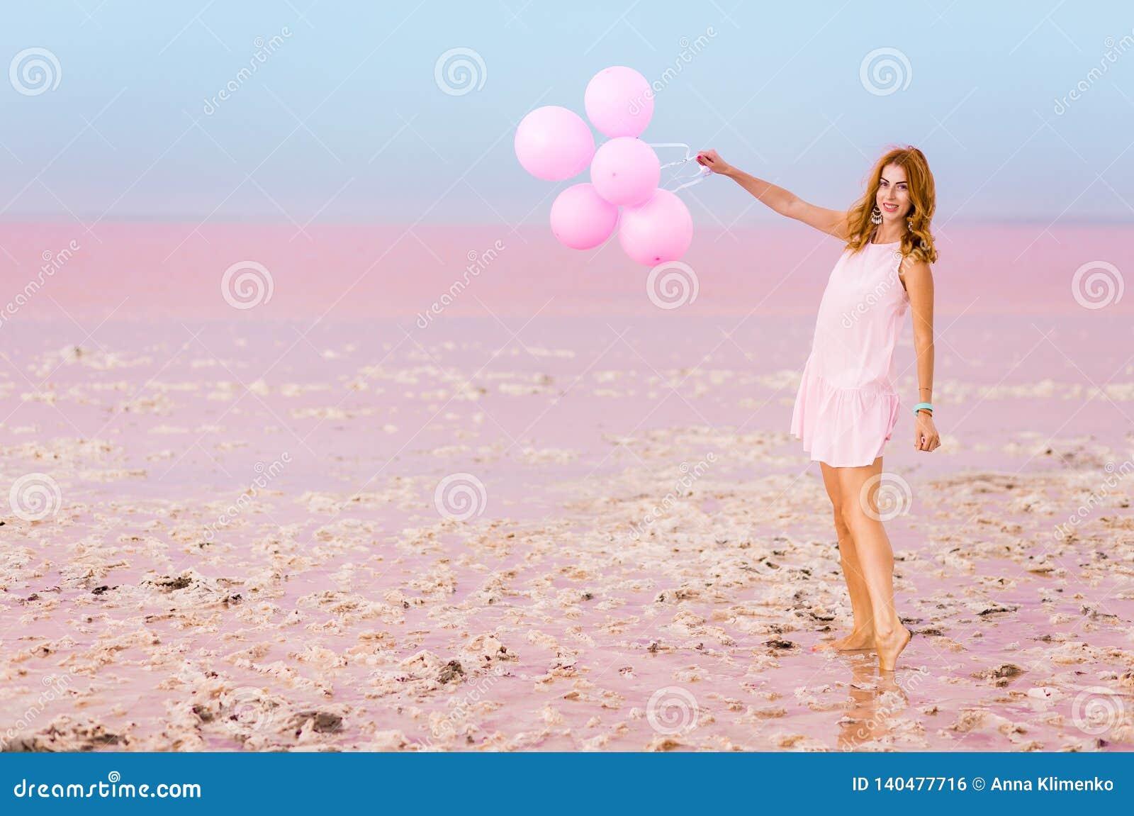 Красивая женщина с baloons на розовом озере соли