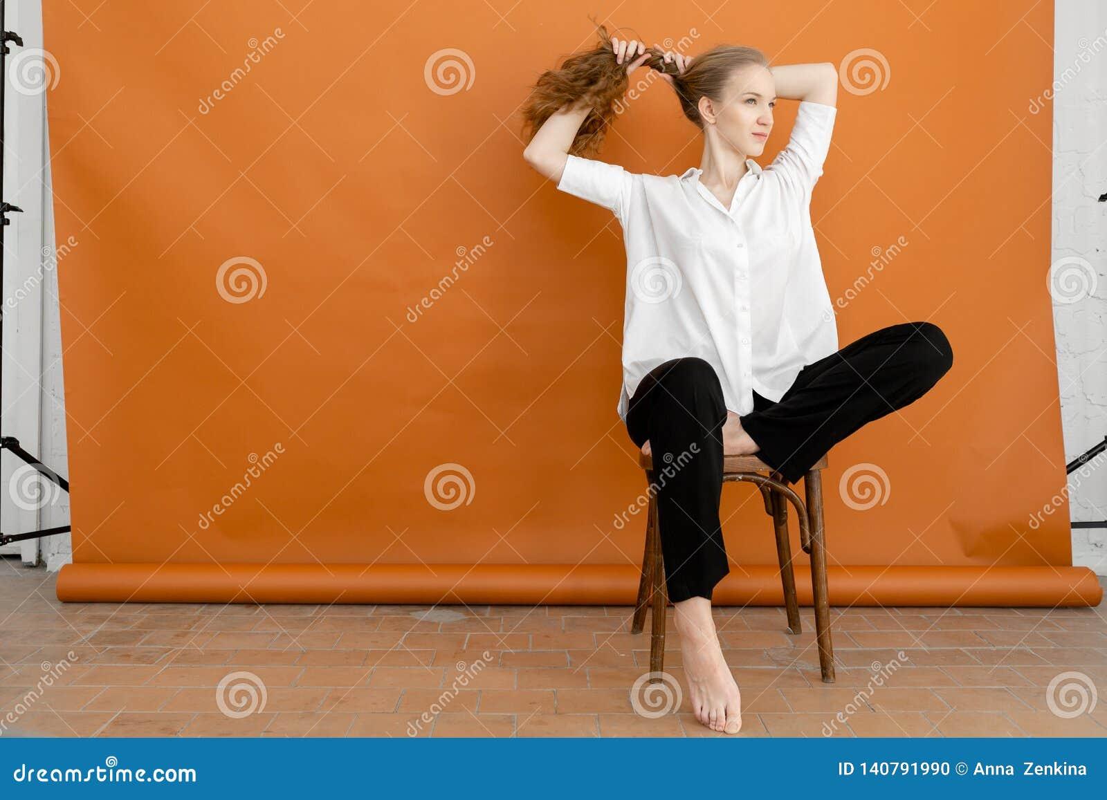 Красивая модель на оранжевой предпосылке сидя на стуле в белой рубашке и черных брюках