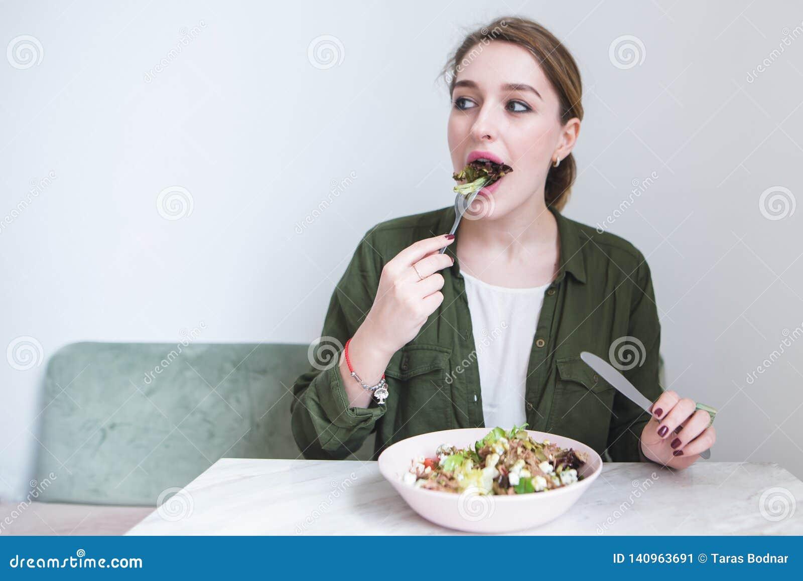 красивая девушка ест салат плиты в светлом ресторане и взгляды к стороне Женщина сдерживает зеленый салат