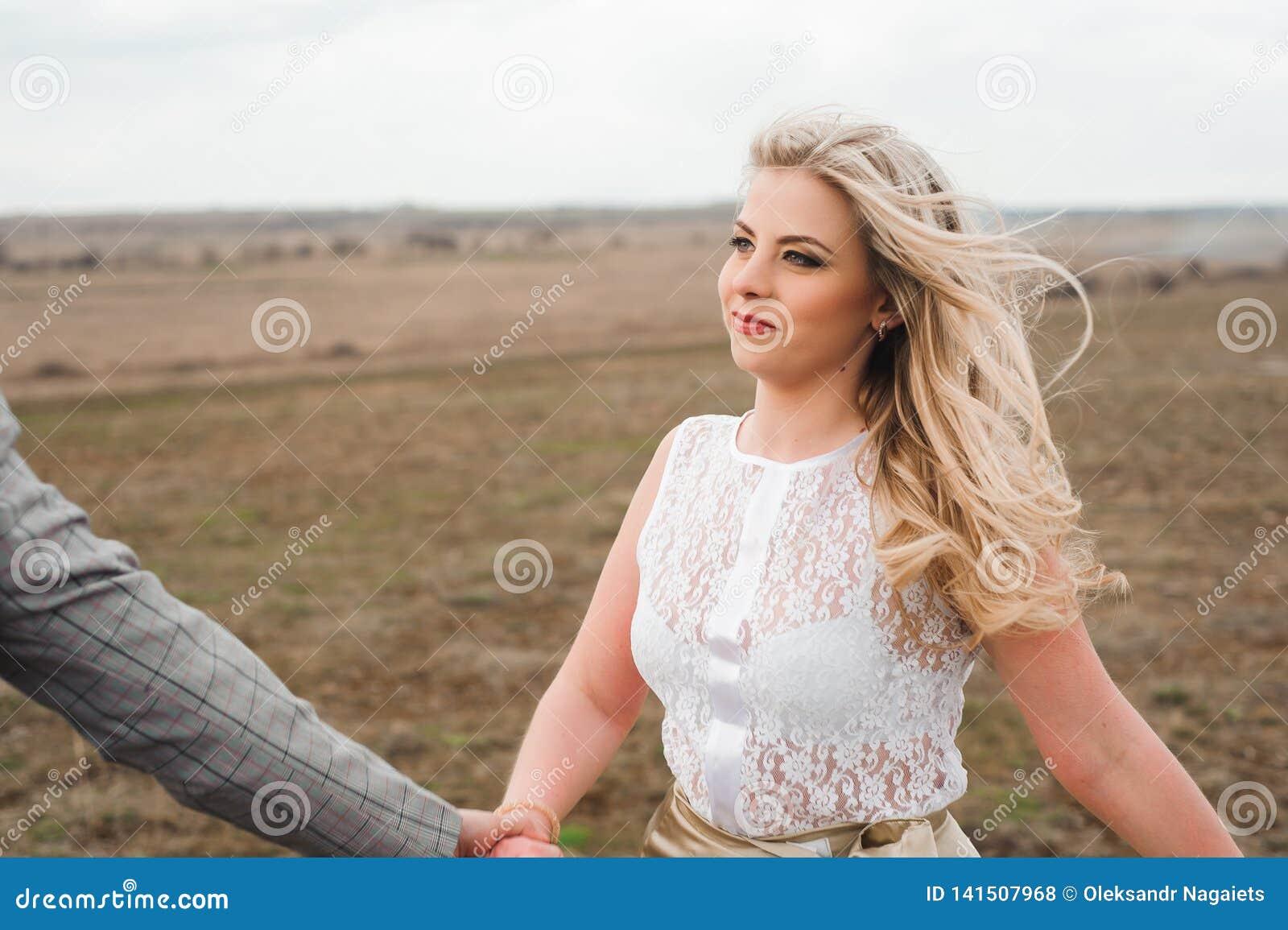 Красивый парень и белокурая девушка идя на поле, человек водят женщину держа руку