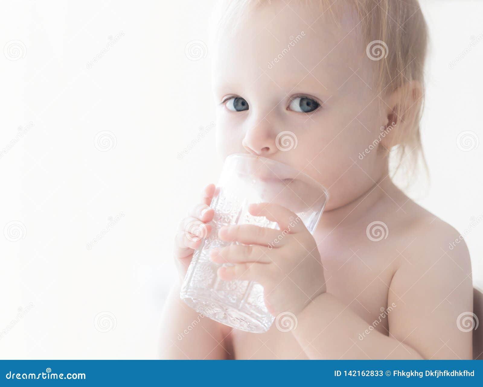 Красивый серьезный сладкий маленький ребенок с глазами каштановых волос карими смотря прочь сидящ на питьевой воде таблицы от неб