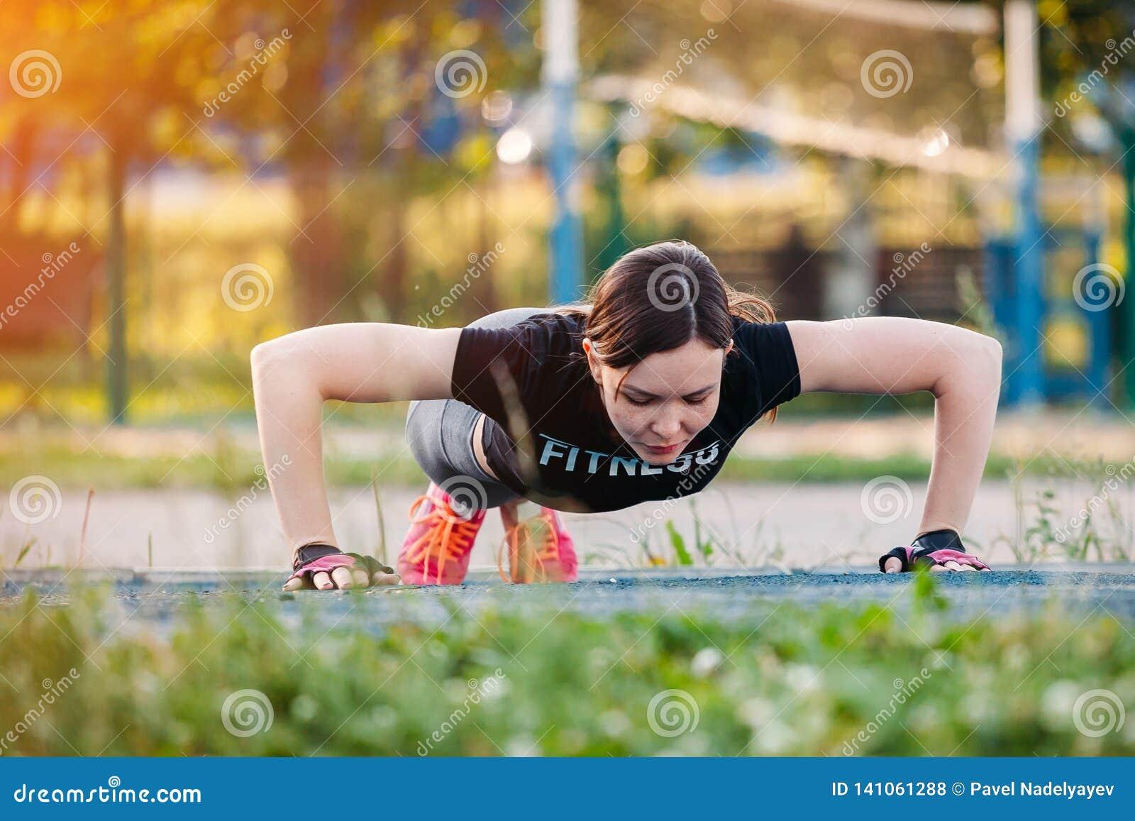 Красивый тонкий брюнет делая некоторое Нажим-поднимает снаружи в парке Женщина фитнеса во время на открытом воздухе разминки пере