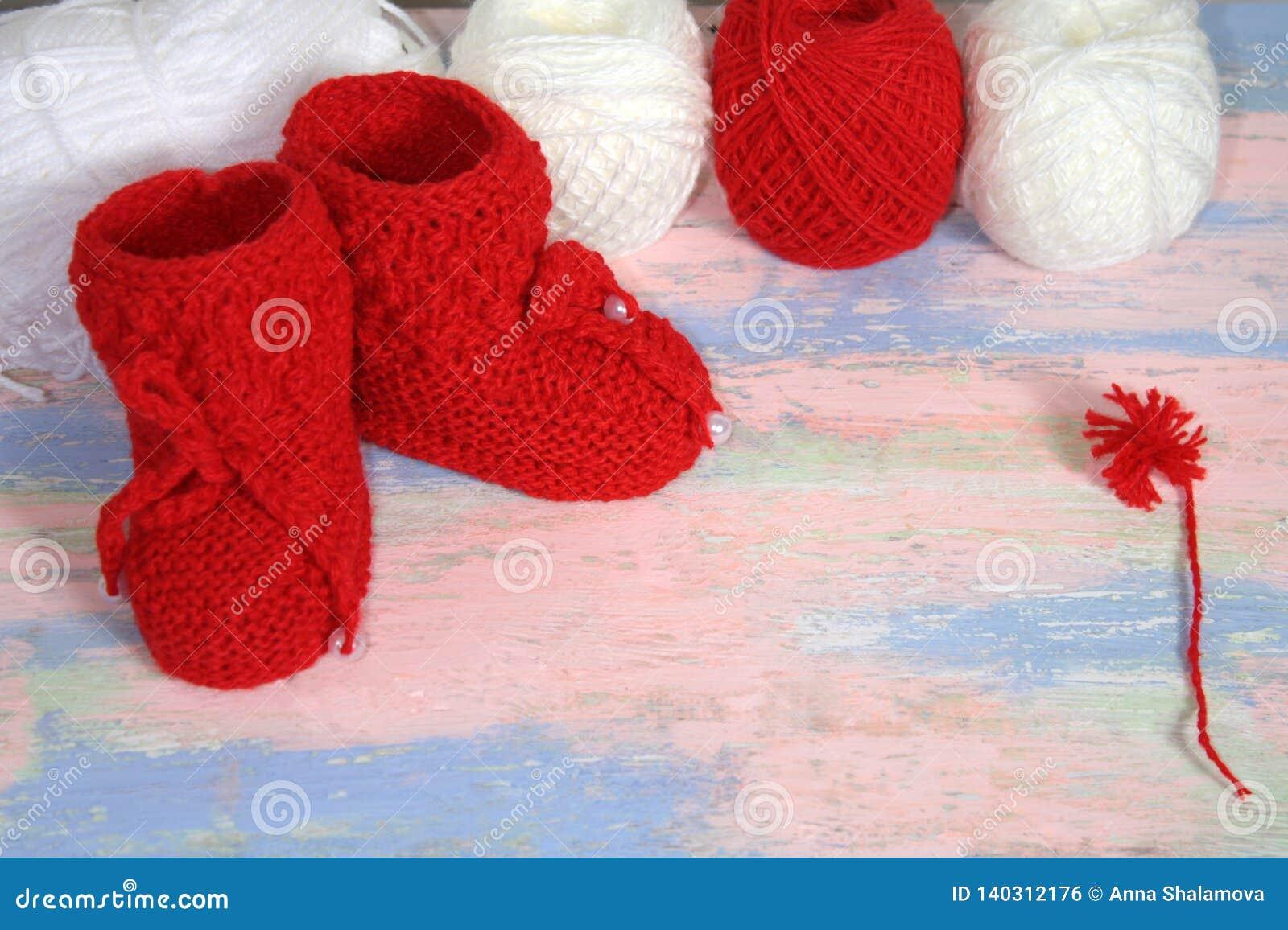 Красные связанные добычи младенца, красные и белые шарики пряжи шерстей для вязать и красного помпона пряжи на пинке - голубой пр