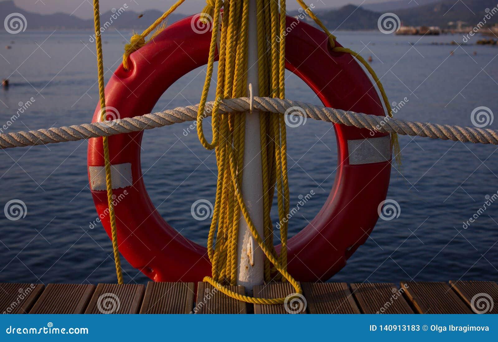 Красные lifebuoy и желтые веревочки висят на пристани