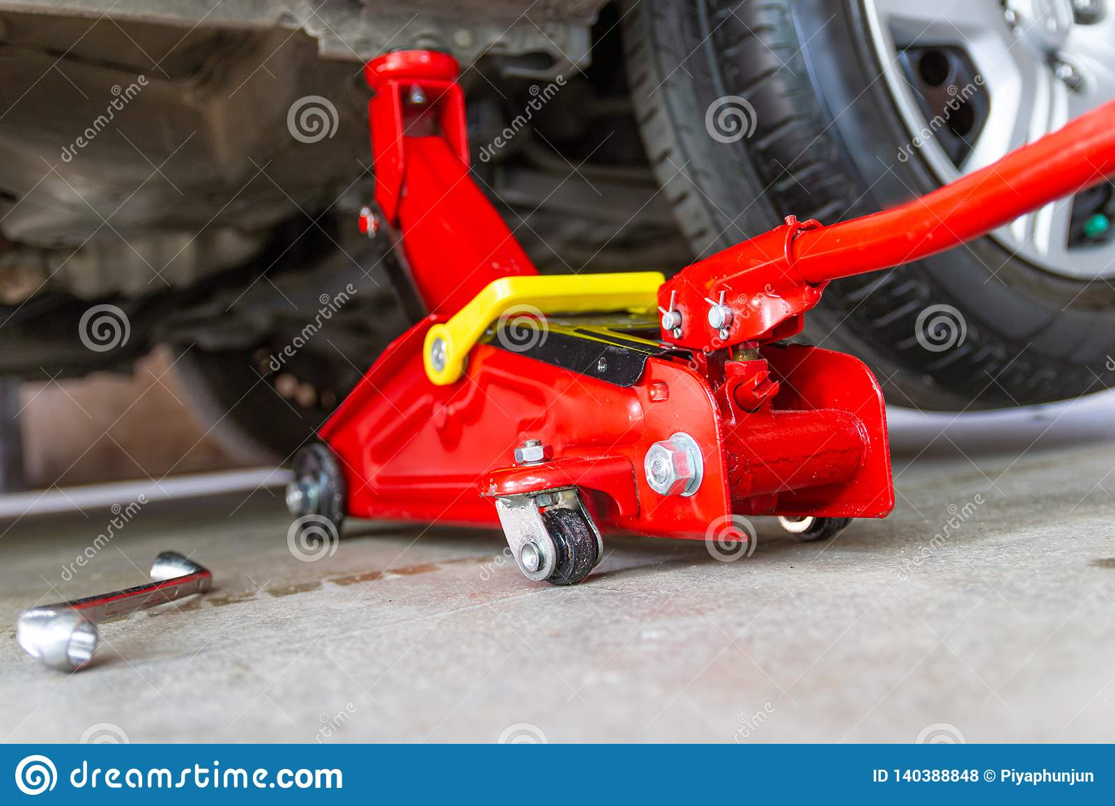 Красный инструмент поднимает автомобиль домкратом подъема для проверки ремонта