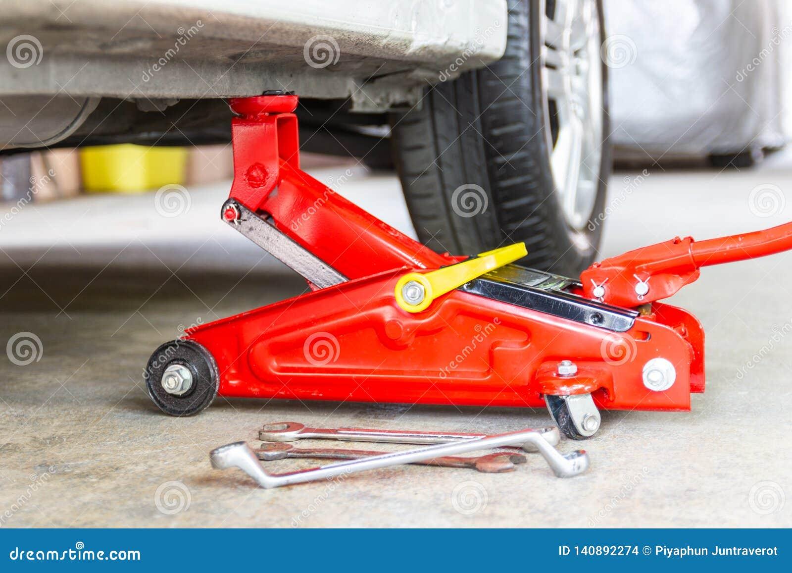 Красный инструмент поднимает автомобиль домкратом подъема для обслуживания проверки ремонта