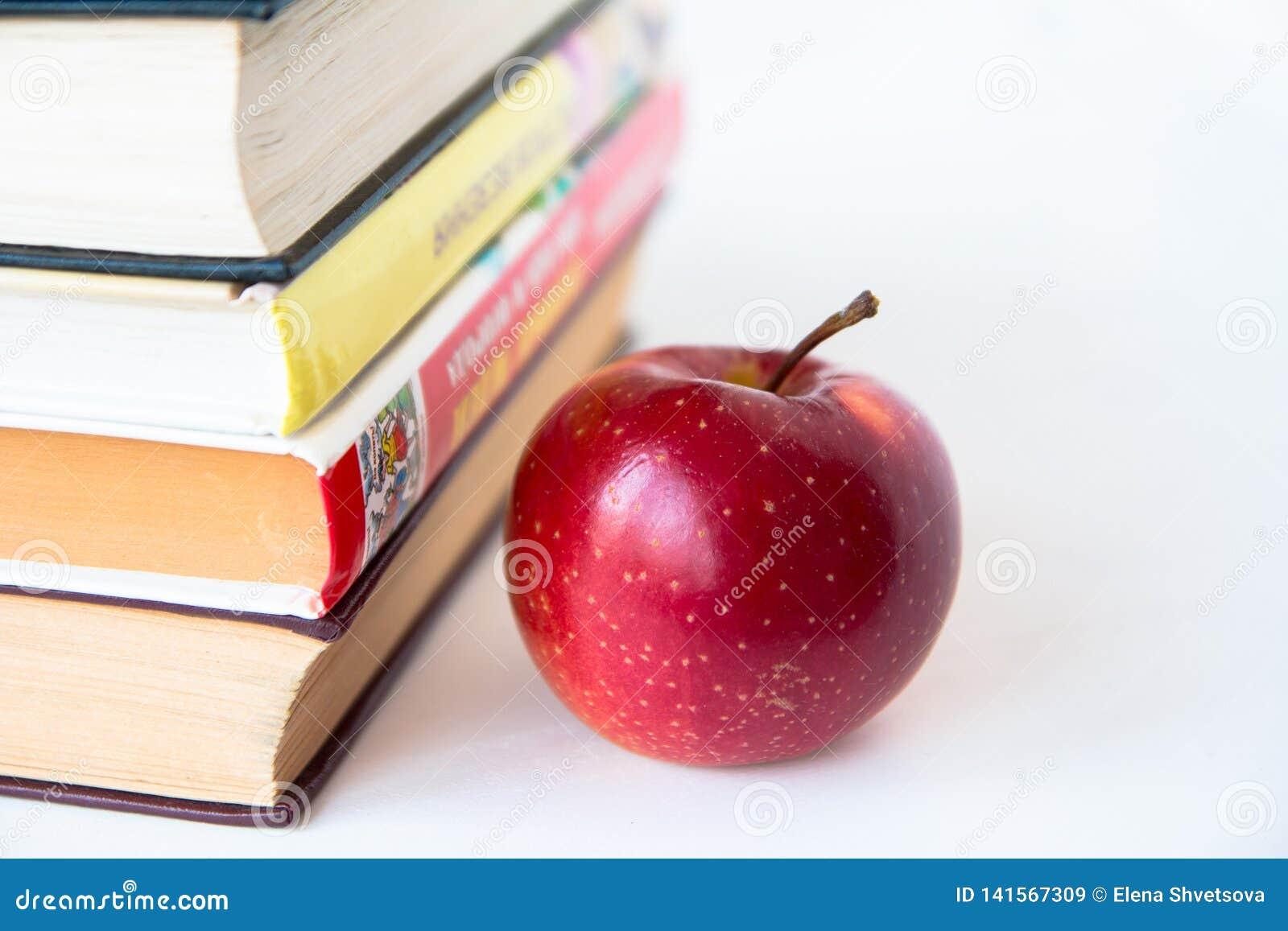 Красное зрелое сочное яблоко около книг
