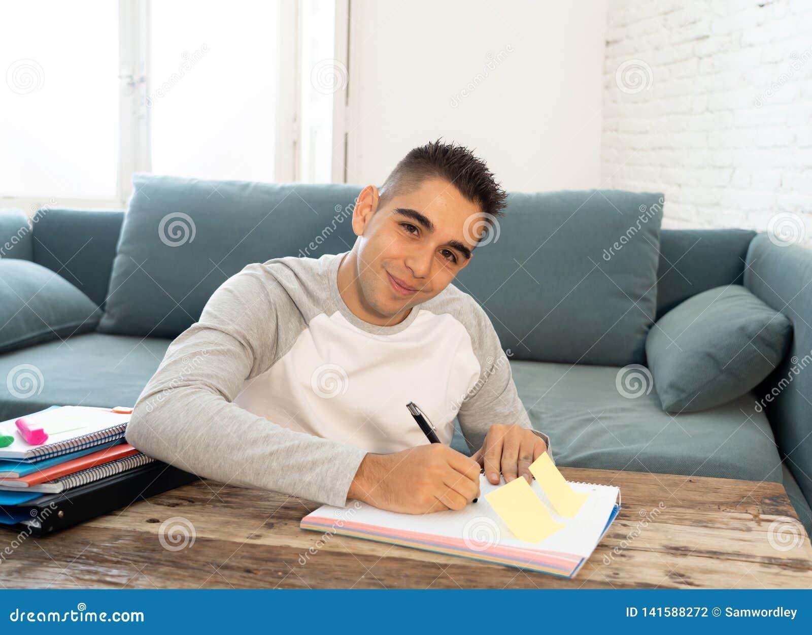 Крупный план счастливый, жизнерадостный изучать молодого человека, работая в домашней работе Учить от книг дома