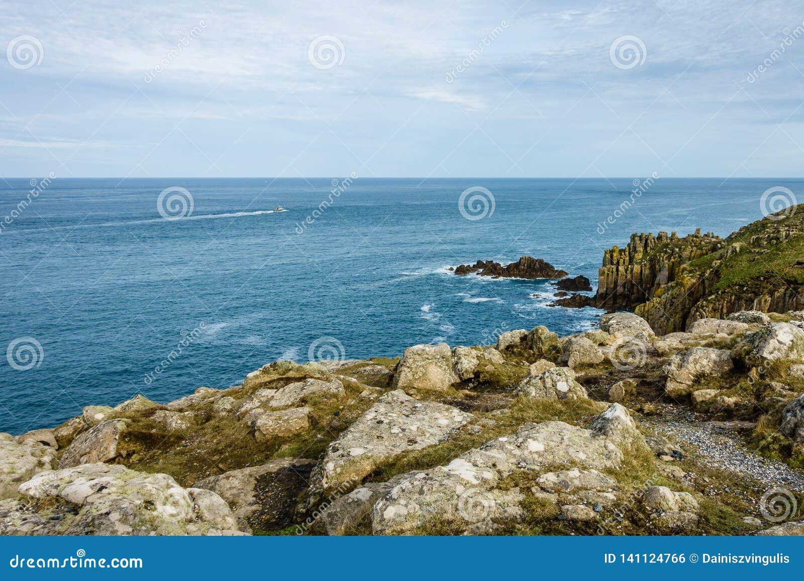 крутое побережье и маленькая лодка на горизонте