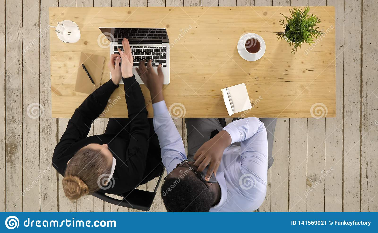 Коммерсантка используя ноутбук и бизнесмен делая работу команды звонка