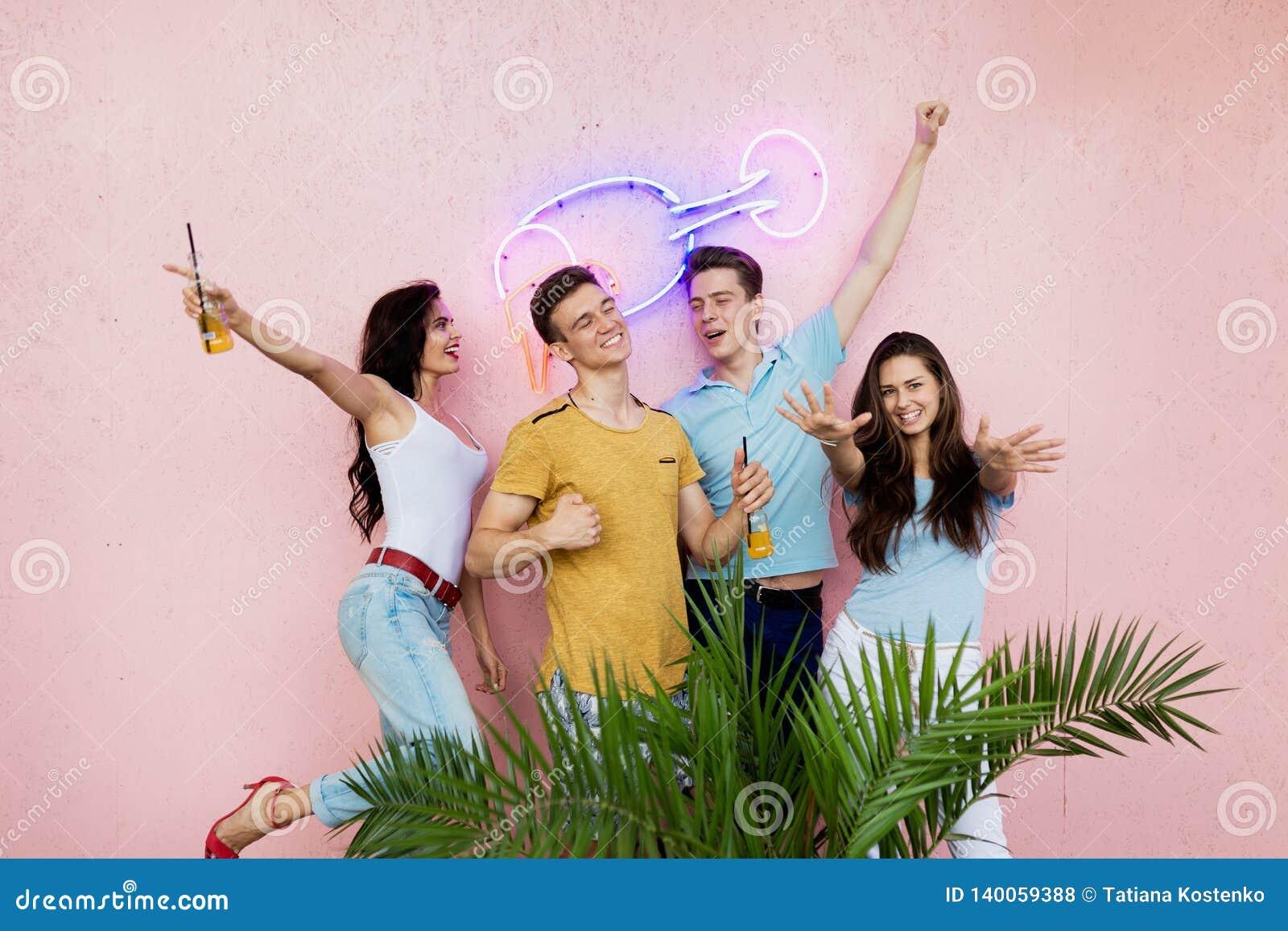 Компания симпатичных друзей смеясь, выпивая желтые коктейли стоит перед розовой стеной и за