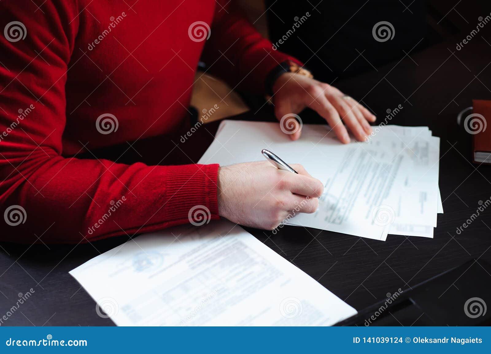 Конец-вверх мужских рук с ручкой над документом