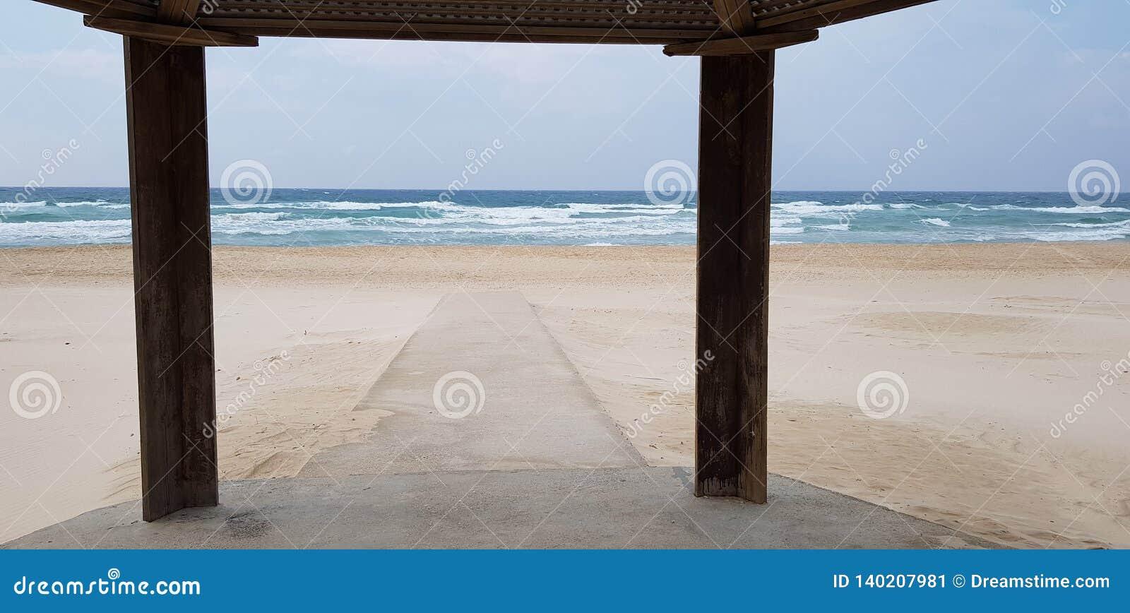 Конкретный след в песке запланированном для людей с ограниченными возможностями идет к морю