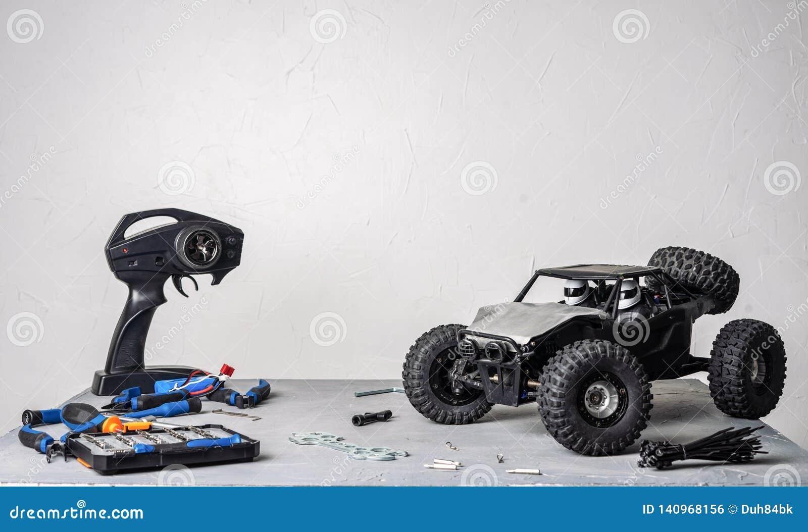 контролируемые Радио модели автомобиля: таблица с разбросанными инструментами для ремонтировать модели rc дефектные и пульт управ