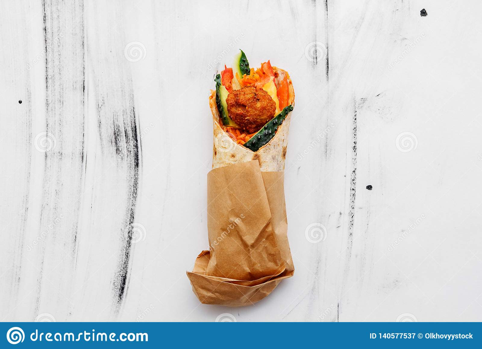 Концепция вегетарианской еды Очень вкусный свежий домодельный вегетарианский tortilla с falafel на деревянном кухонном столе улиц