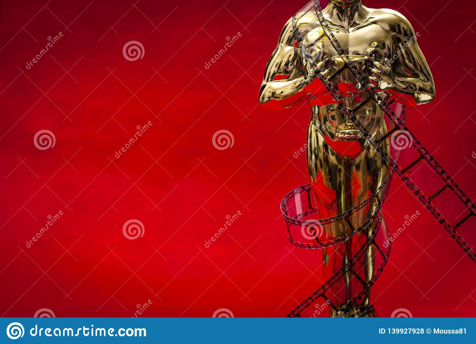 Концепция наград фильма Голливуд с сияющей металлической наградой фильма в оболочке в прокладке фильма целлулоида на красном ковр
