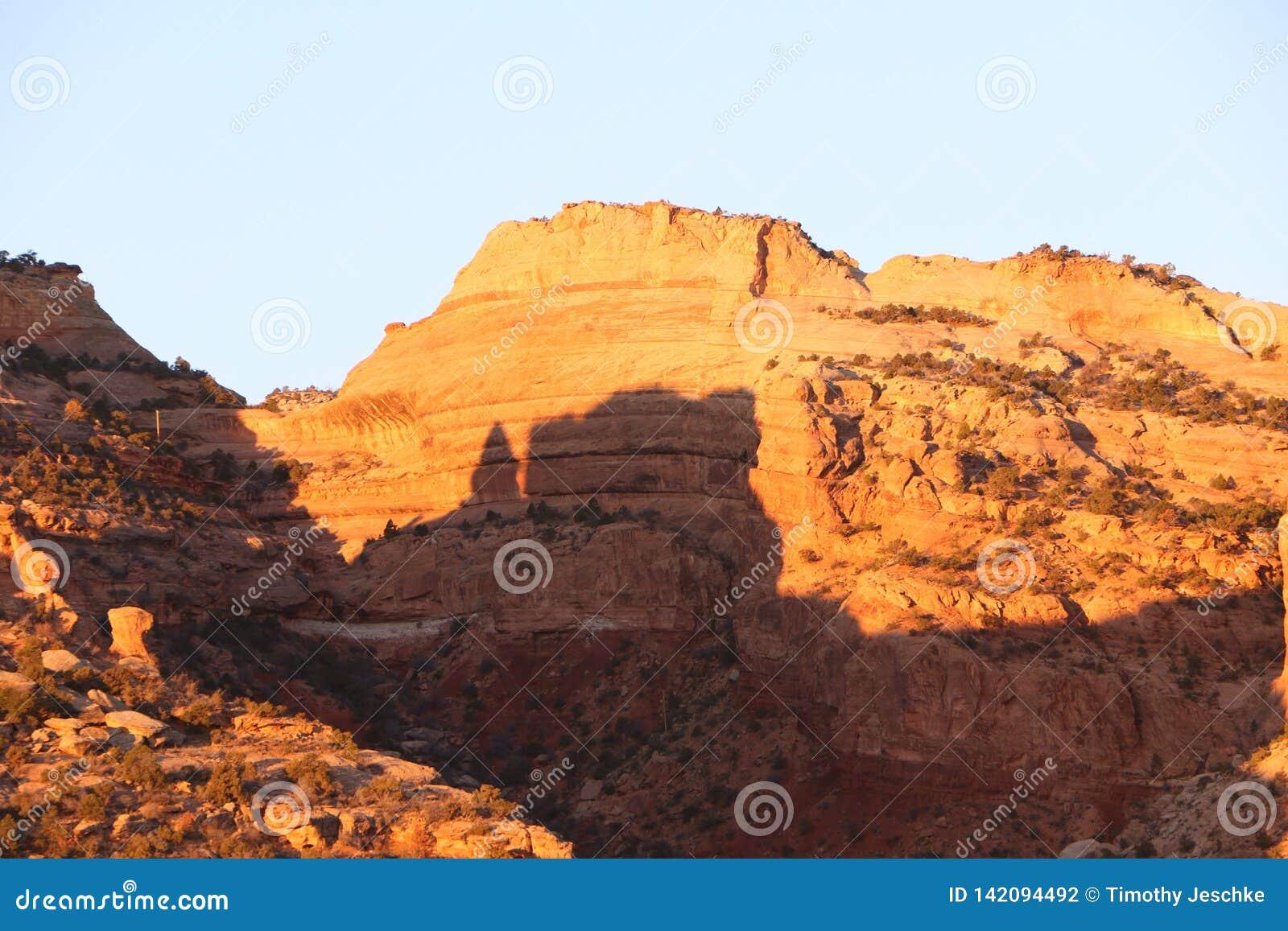 Ландшафт Sunlit пустыни скалистый на зоре