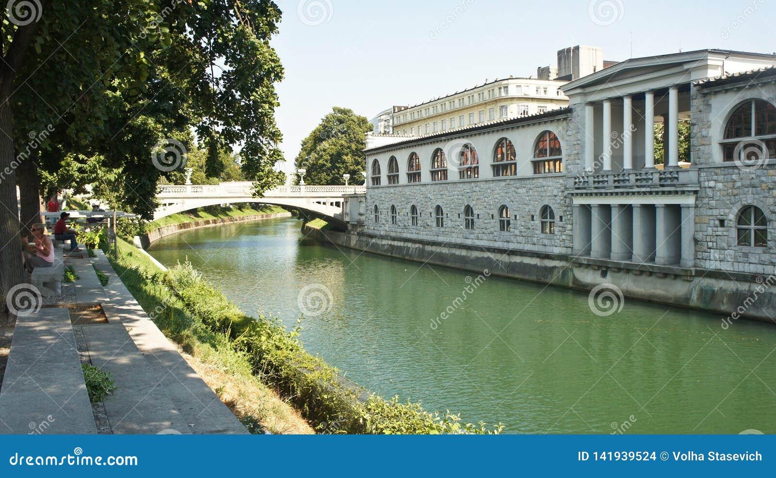 Любляна, Словения - 07/19/2015 - взгляд обваловки реки Ljubljanica в старом городке, городском пейзаже с мостом, красивым