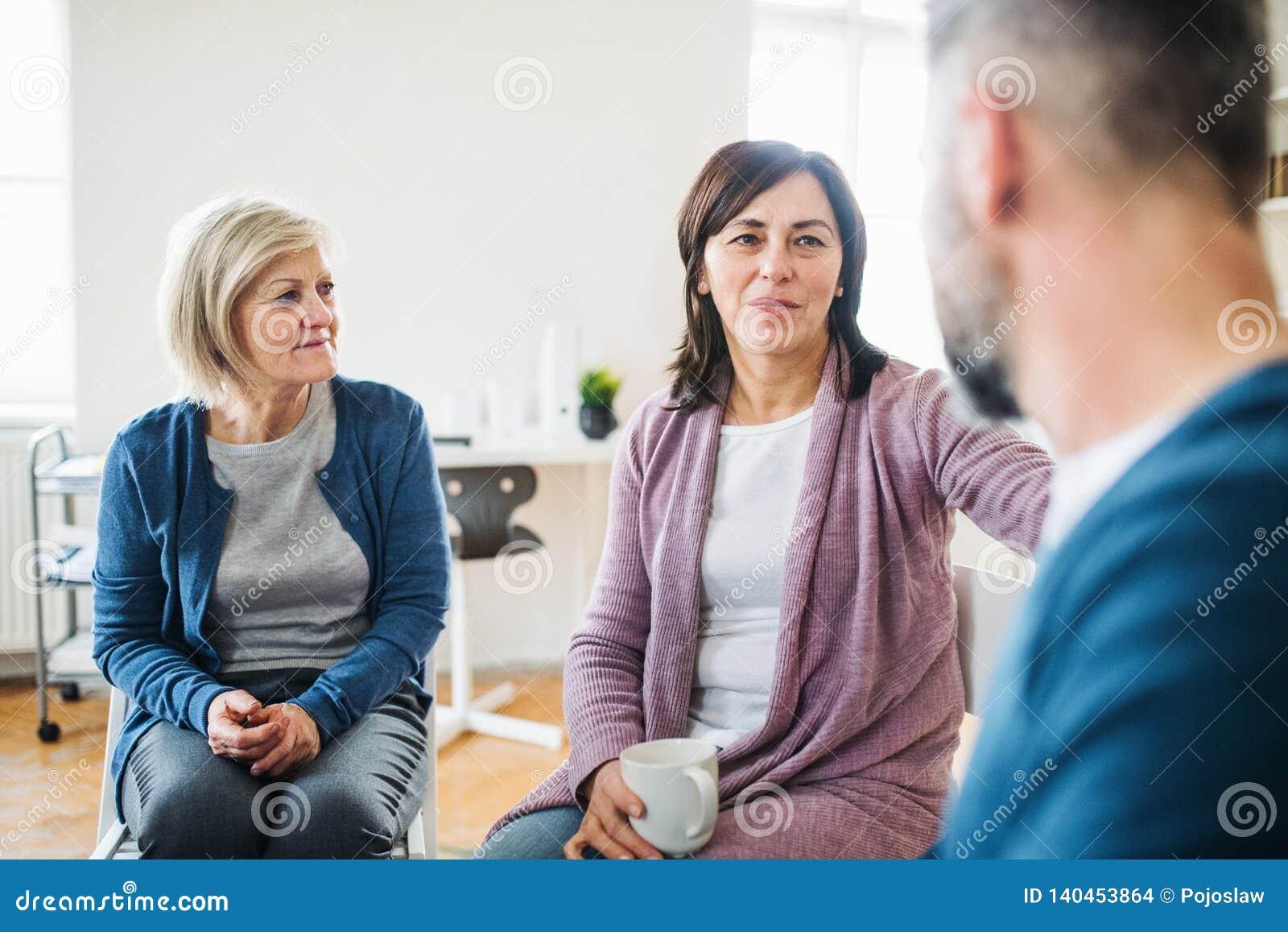 Люди и женщины сидя в круге во время терапии группы, поддерживая одина другого