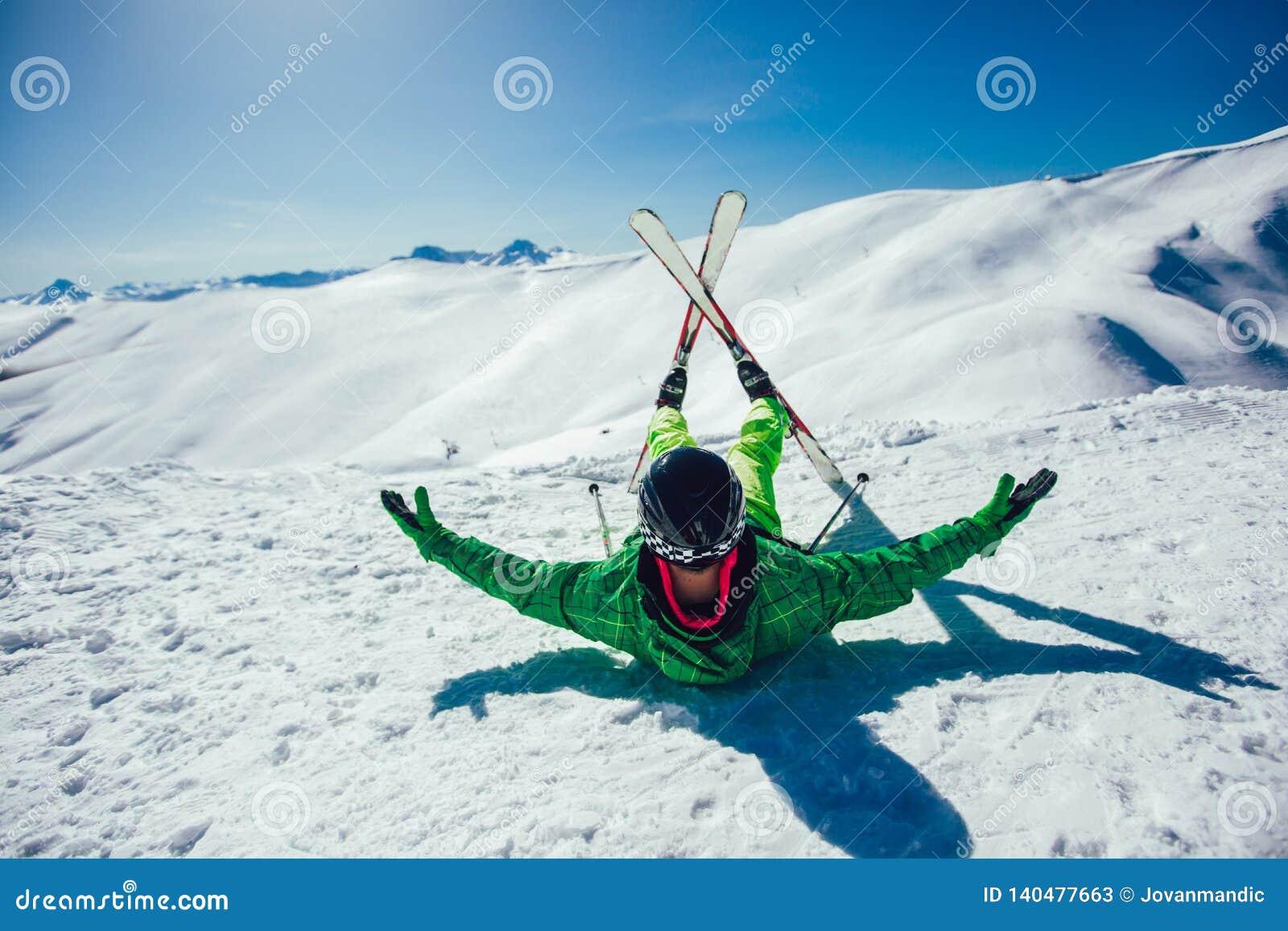 Лыжник лежа на горнолыжном склоне на солнечном дне