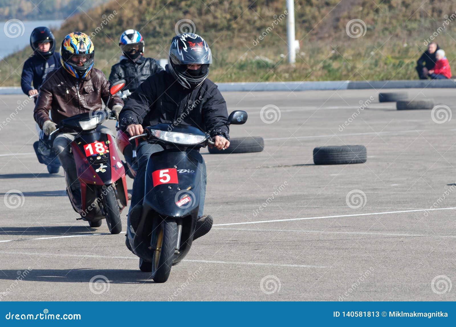 Магнитогорск, Россия, - 28-ое сентября 2014 Молодые члены клуба вентиляторов скутеров держат гонки тренировки на открытое городск