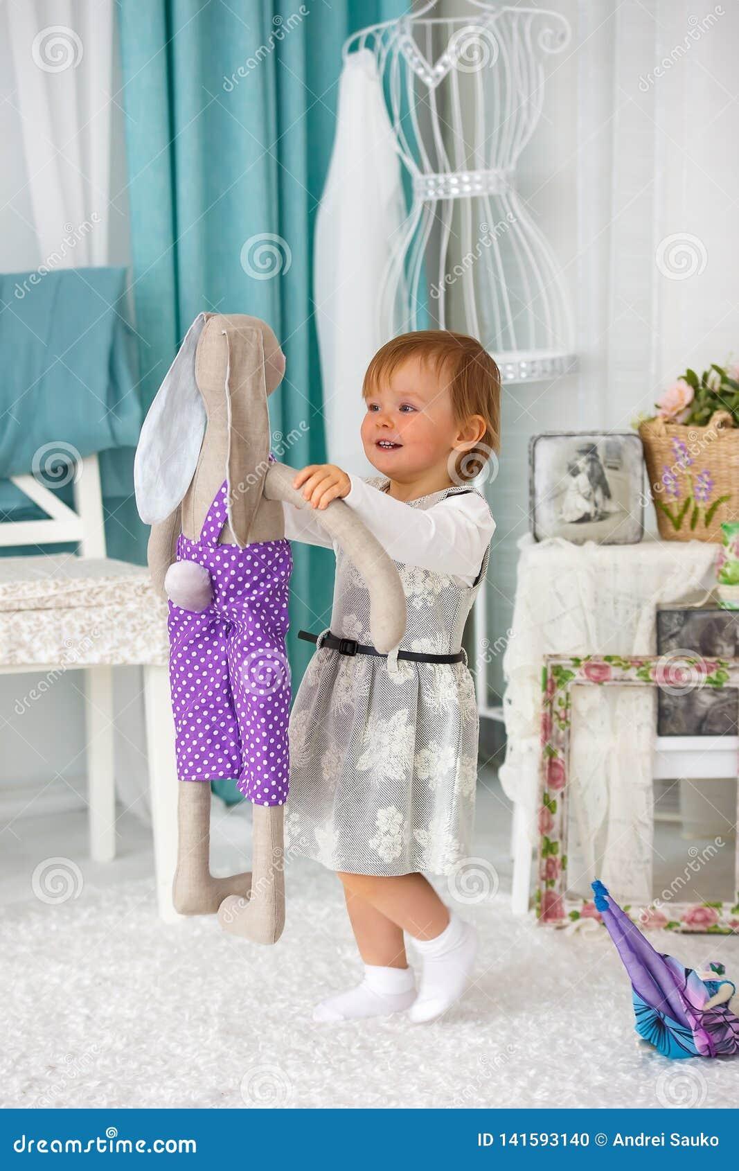 Маленькая девочка играя с куклой и усмехаться