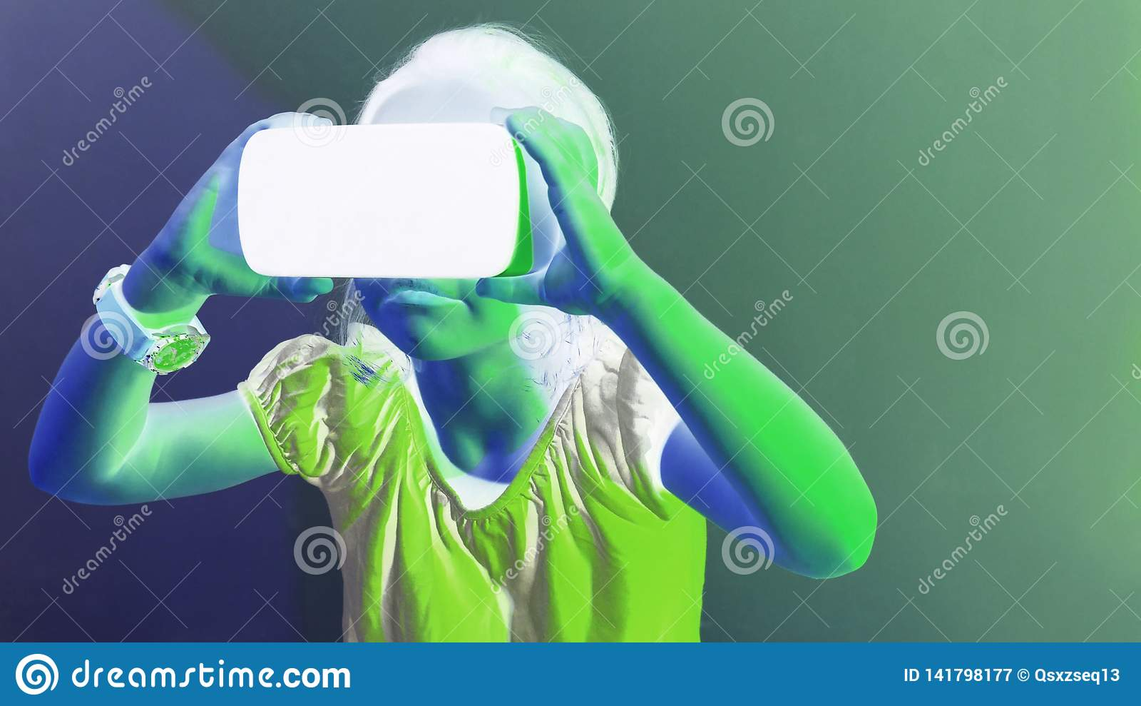 Маленькая девочка испытывая игру шлемофона VR на красочной предпосылке технология фактически