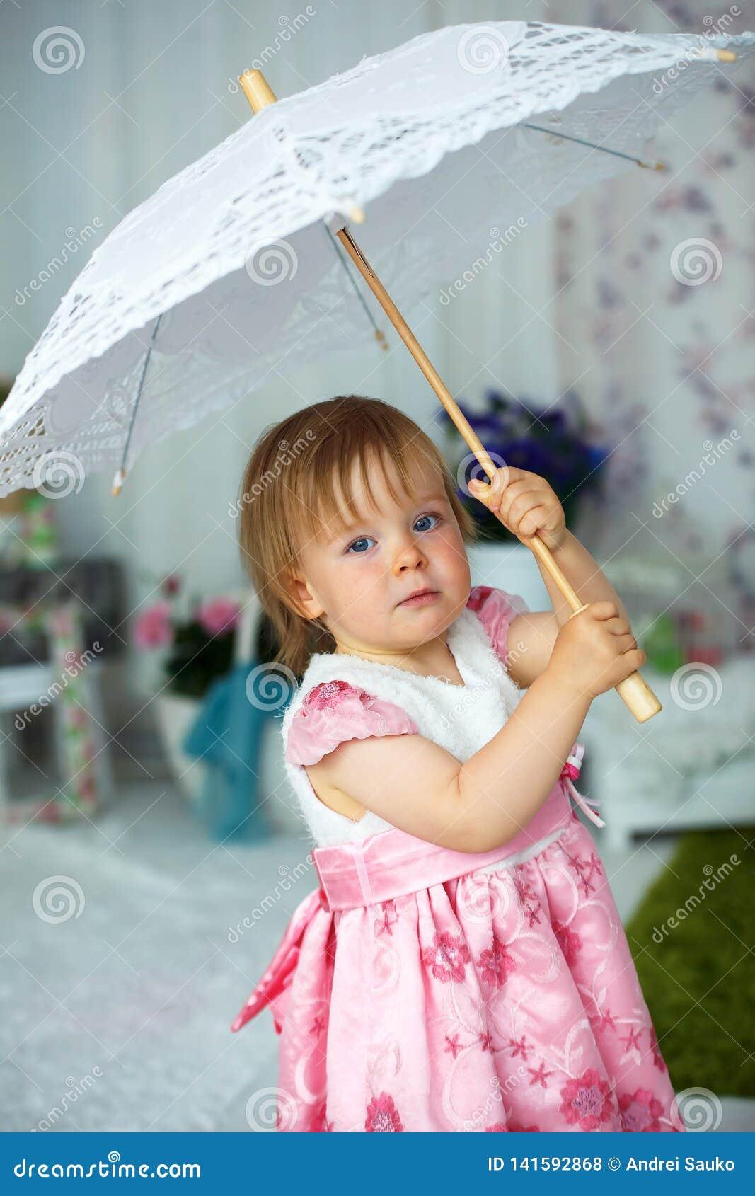 Маленькая девочка держа зонтик для солнца