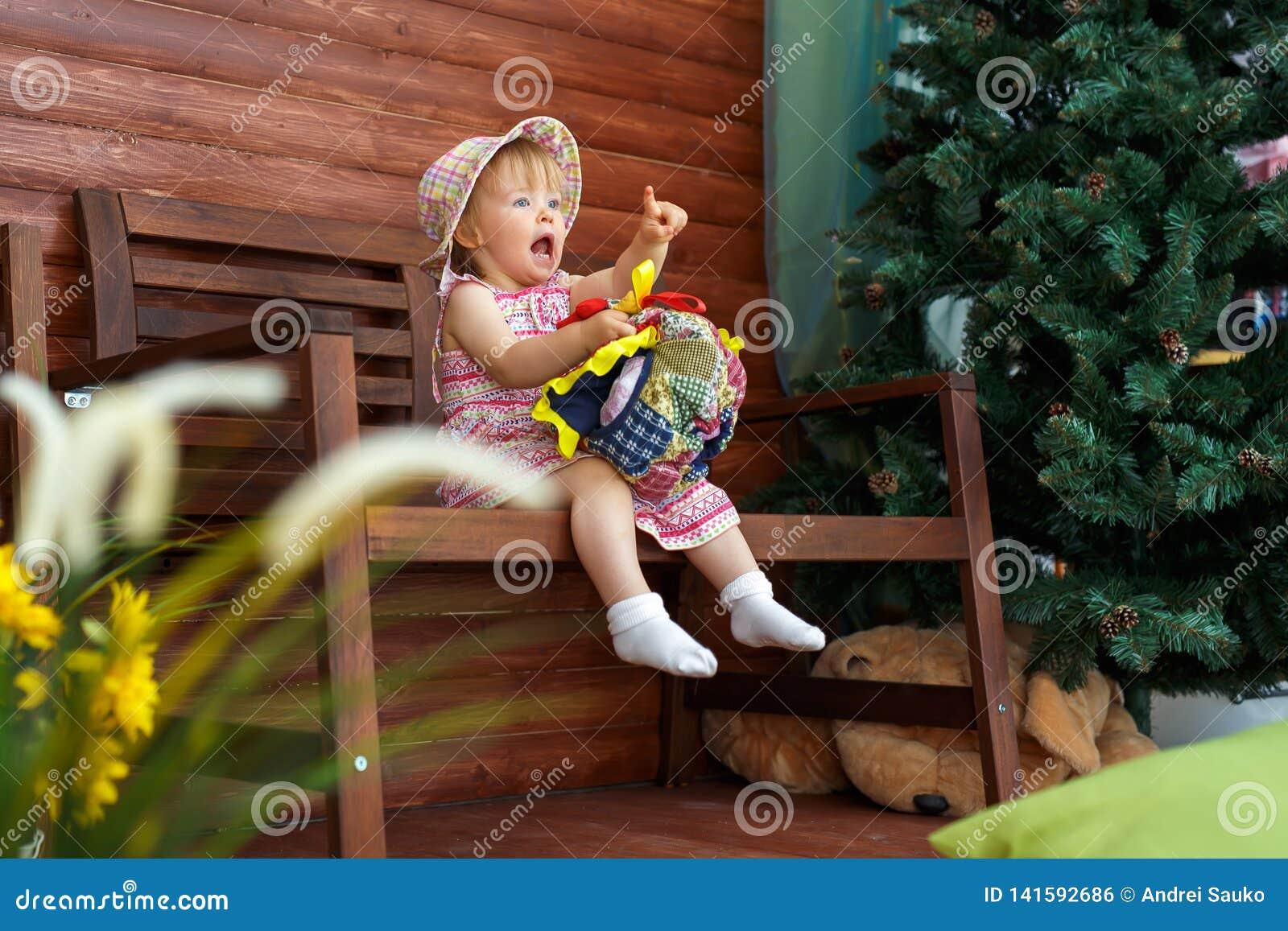 Маленькая девочка сидит и усмехается