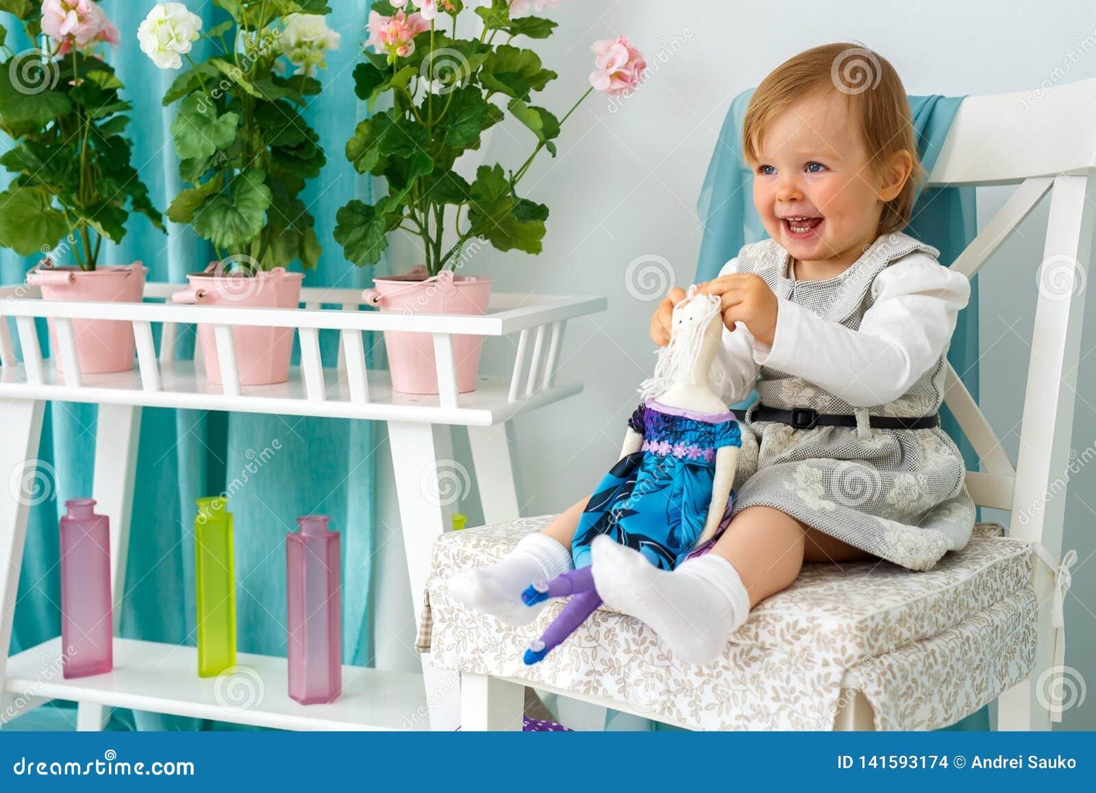 Маленькая девочка сидит на больших стуле и усмехаться