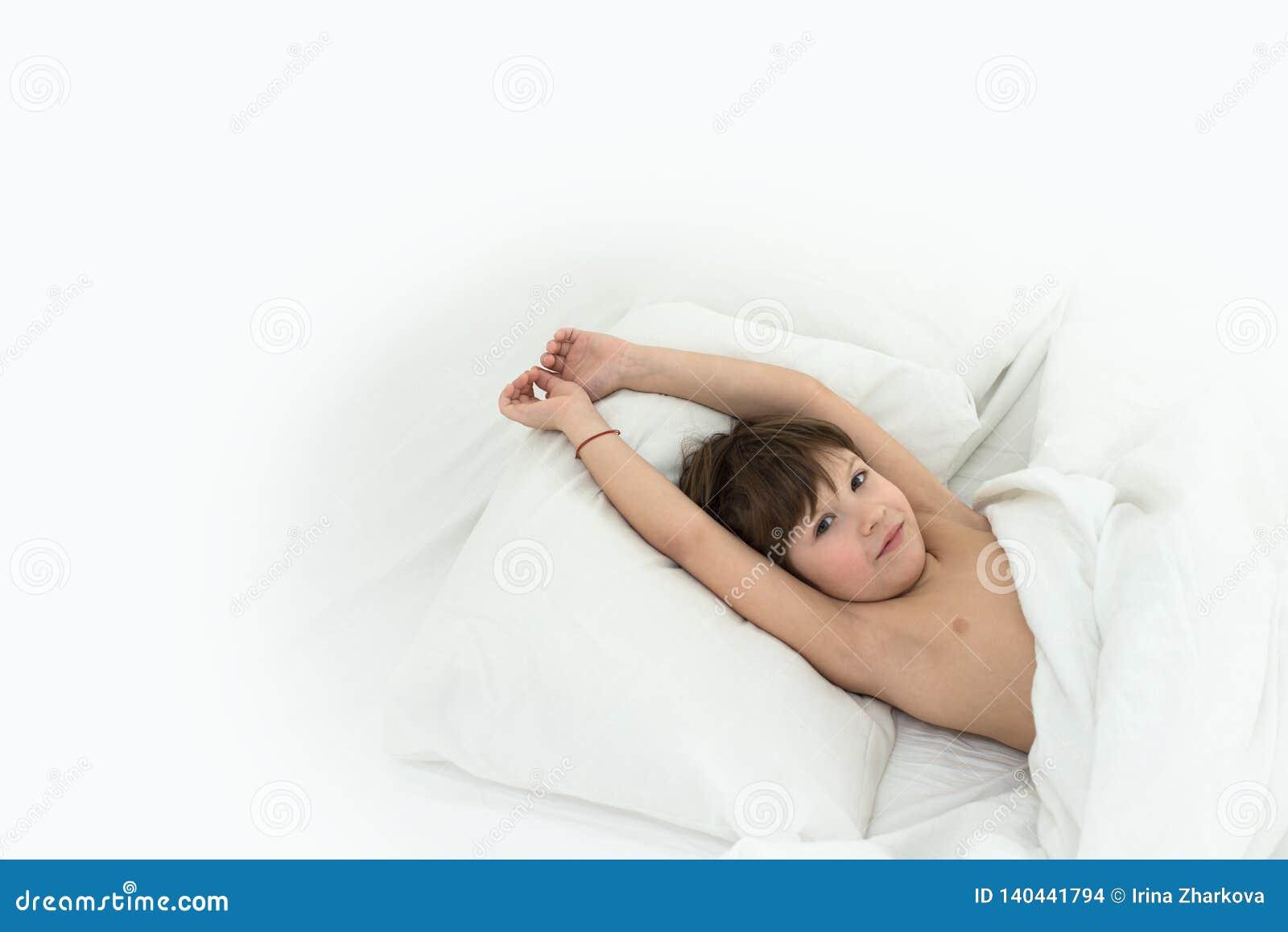 Мальчик лежит в кровати на белые постельные белья смещать ребенок