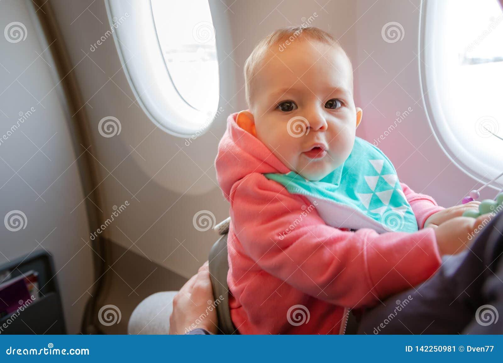 Мать и младенец сидя совместно в самолете Первый полет младенческой девушки Она изумлена