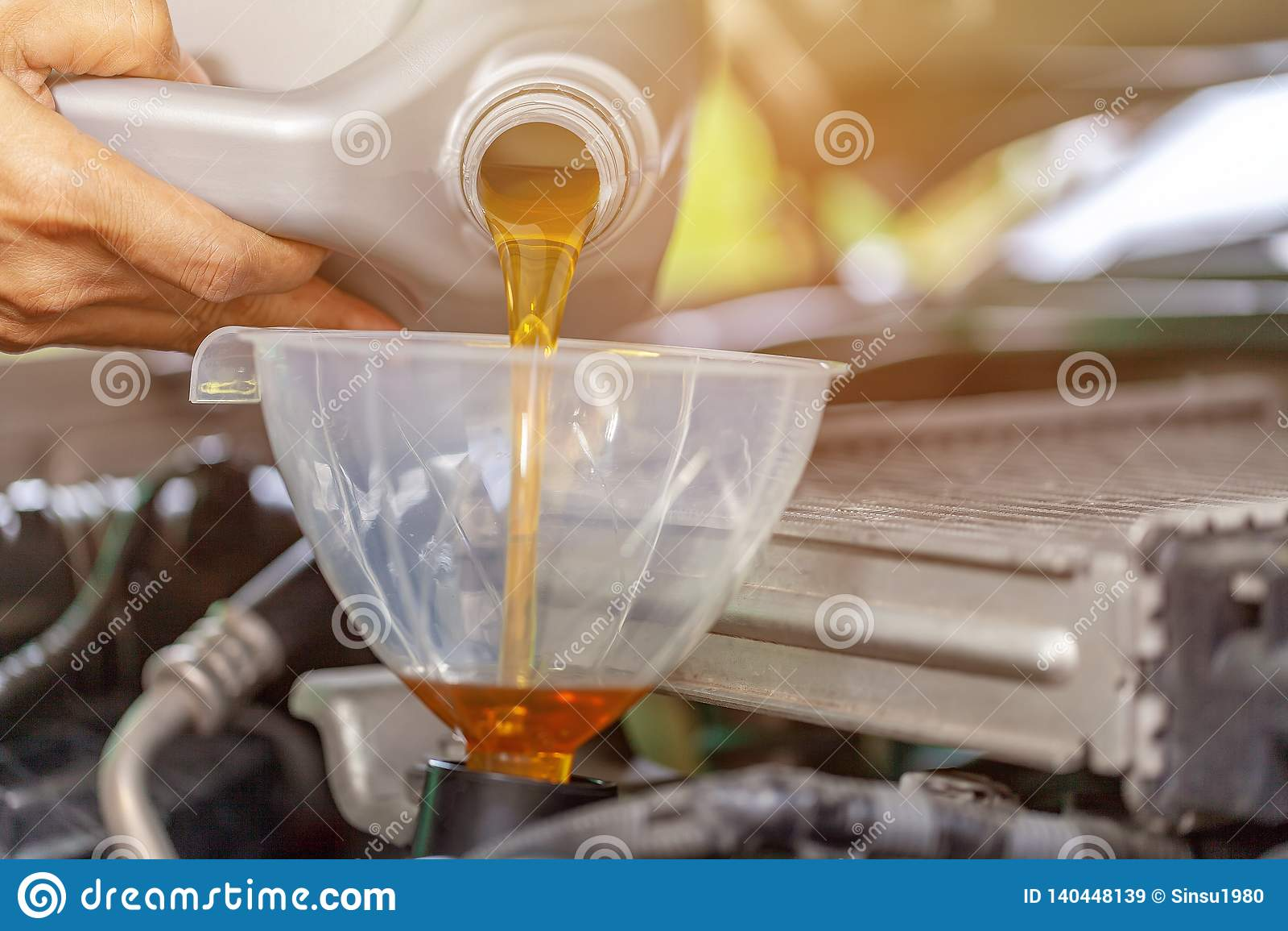 Механик обслуживать обслуживания автомобиля лить новую смазку масла в двигатель автомобиля Селективный фокус
