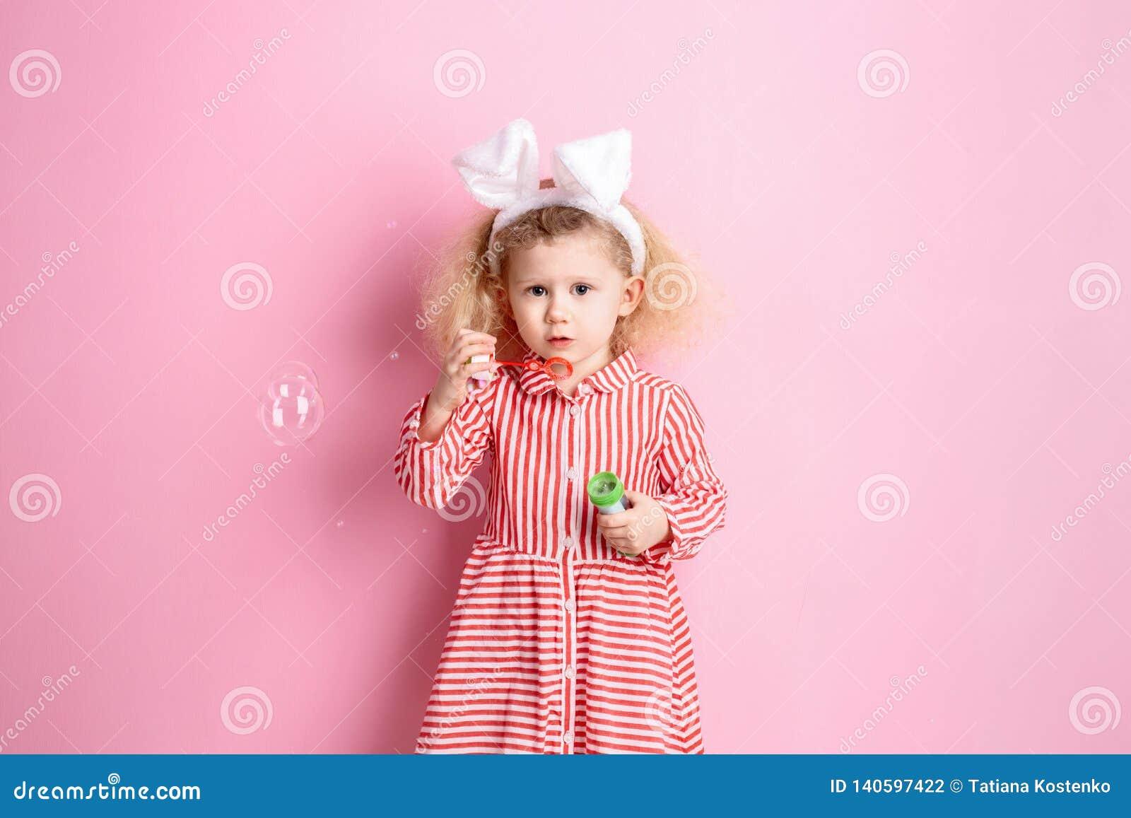 Милая маленькая девочка в striped красных и белых ушах платья и зайчика на ее голове надувает пузыри мыла стоя против a
