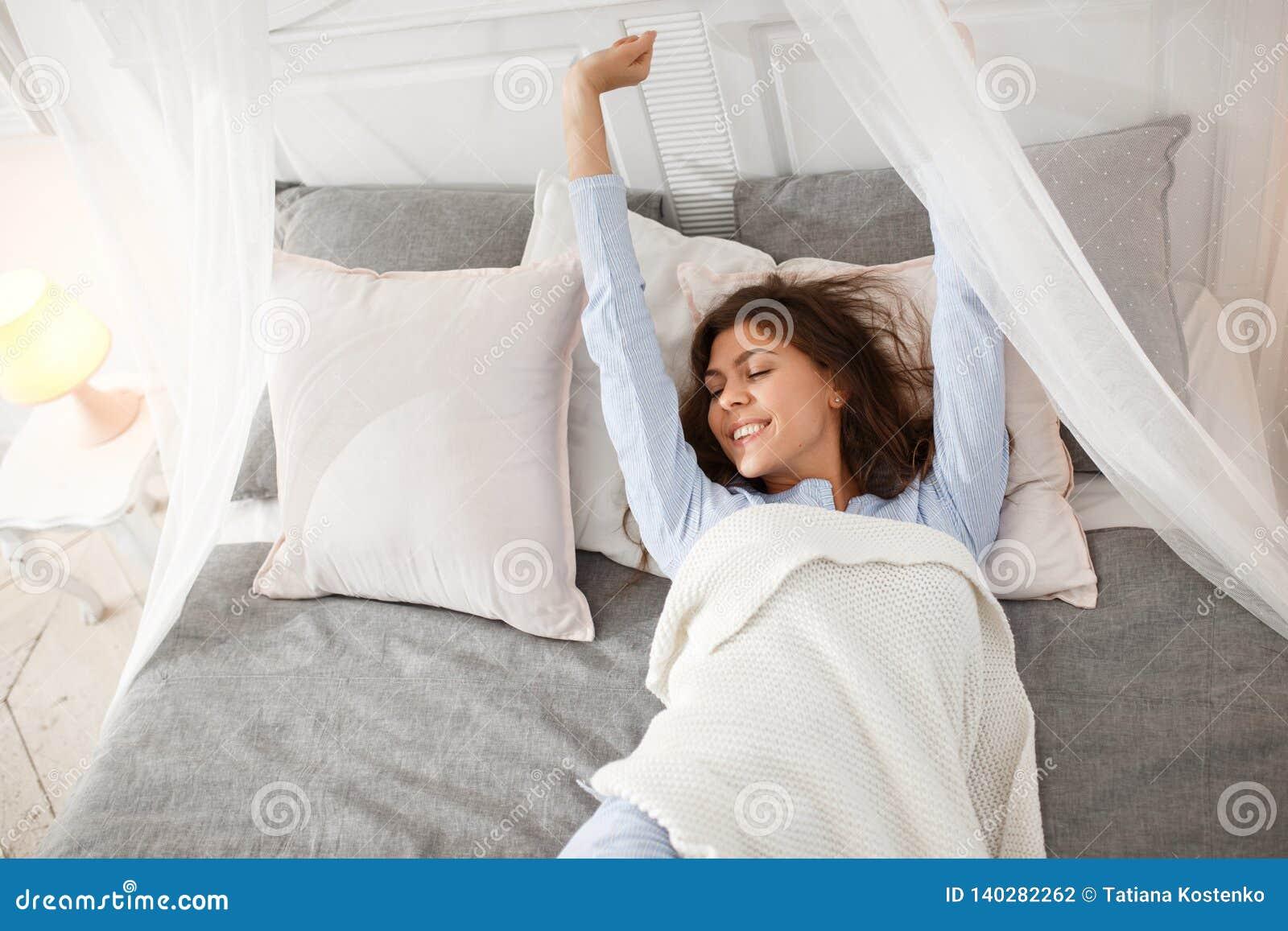 Милая девушка брюнета в свет-голубой пижаме просыпает вверх на кровати сени под бежевым одеялом на сером листе
