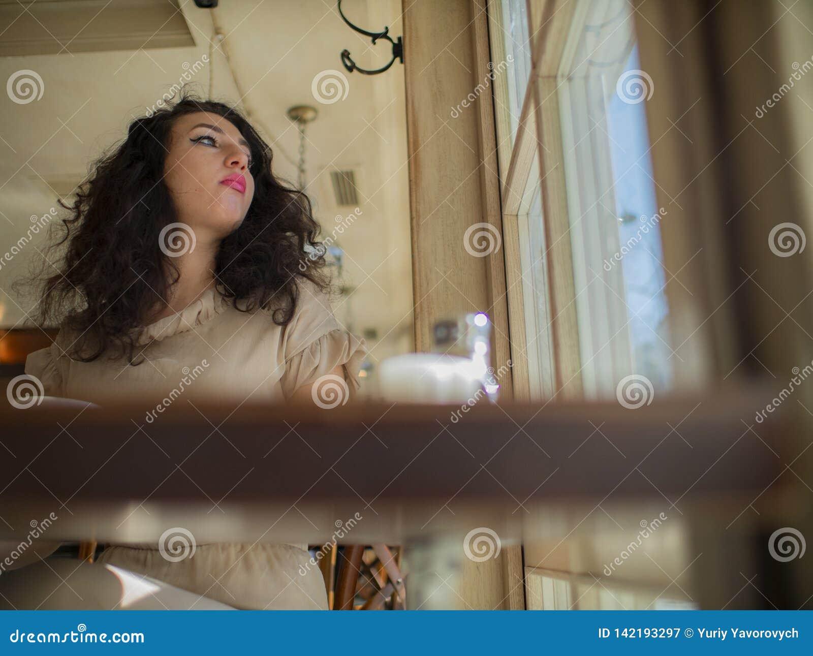 Милая девушка с вьющиеся волосы сидит на таблице в кафе и смотрит вне окно