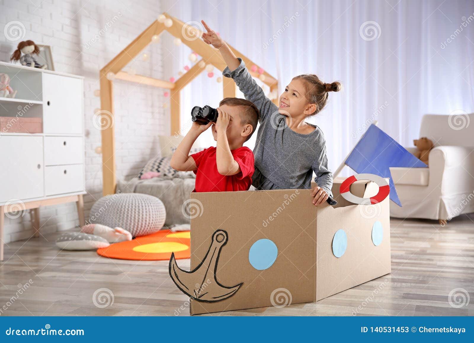 Милые маленькие ребята играя с биноклями и шлюпкой картона