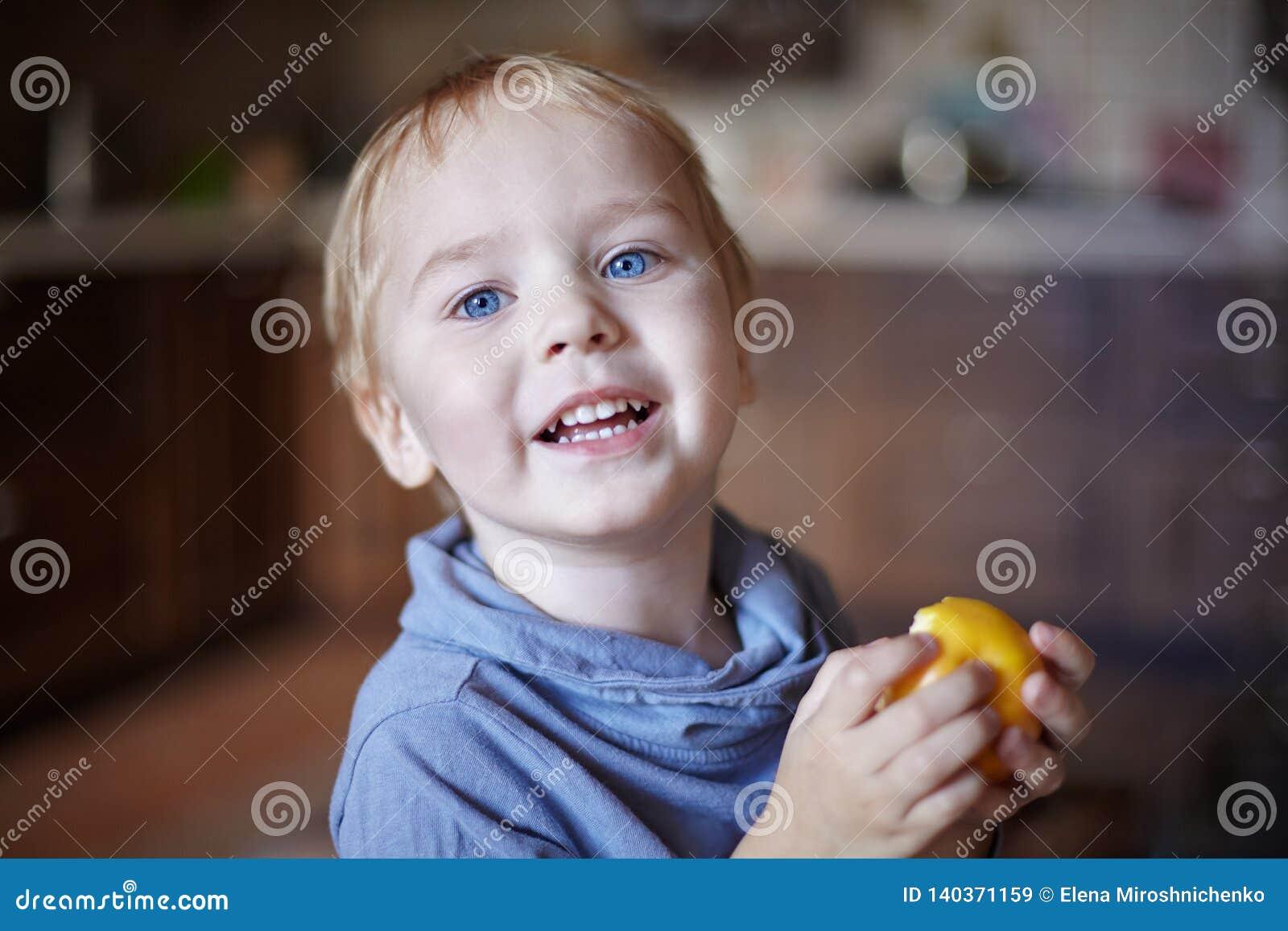Милый кавказский мальчик с голубыми глазами и светлыми волосами ест желтое яблоко, держащ его на руках, усмехаясь