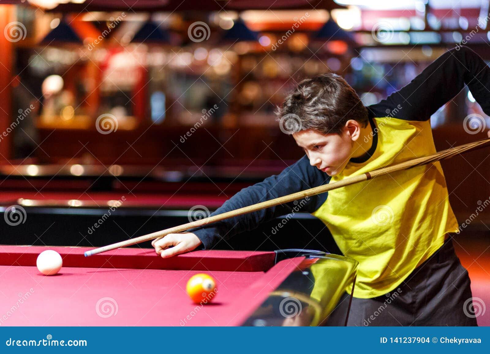 Милый мальчик в желтом билльярде игр футболки или бассейн в клубе Молодой парень учит сыграть снукер Мальчик с сигналом билльярда