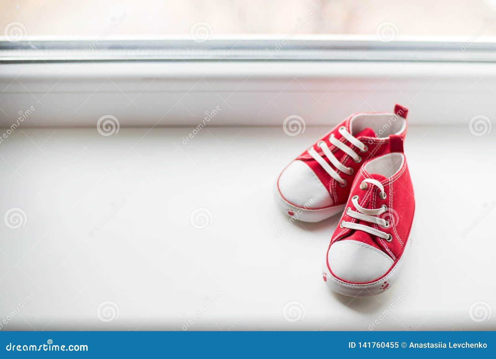 Милое красное малое размером с взгляд сверху ботинок холста на белой предпосылке с copyspace